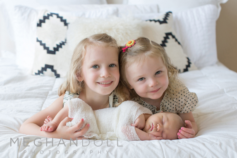 sisters-on-bed-with-baby-brother