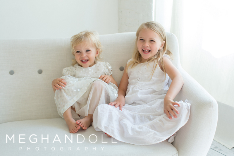 two-little-girls-sitting-by-window-on-white-couch