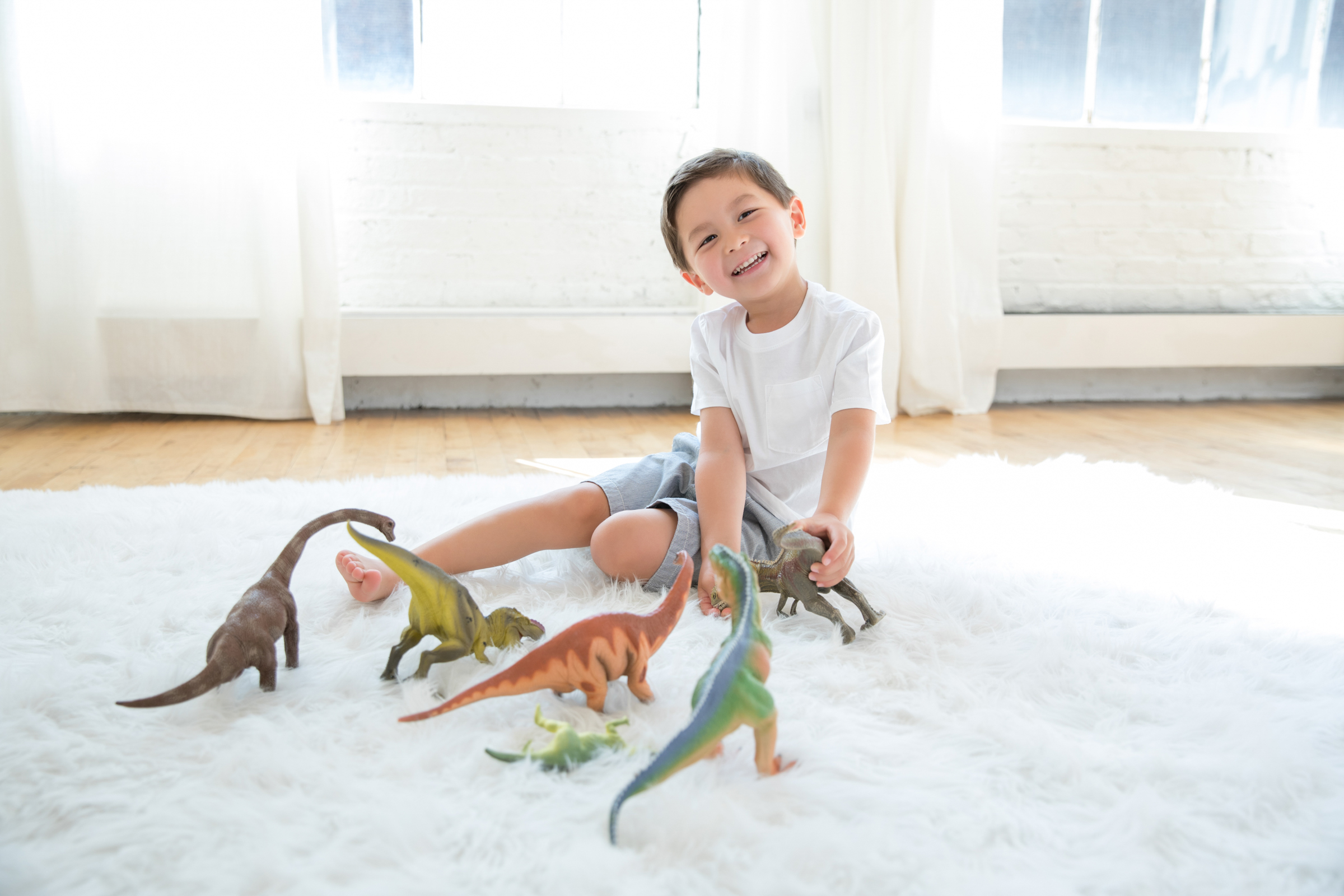 Happy_Boy_Playing_With_Dinosaurs.jpg