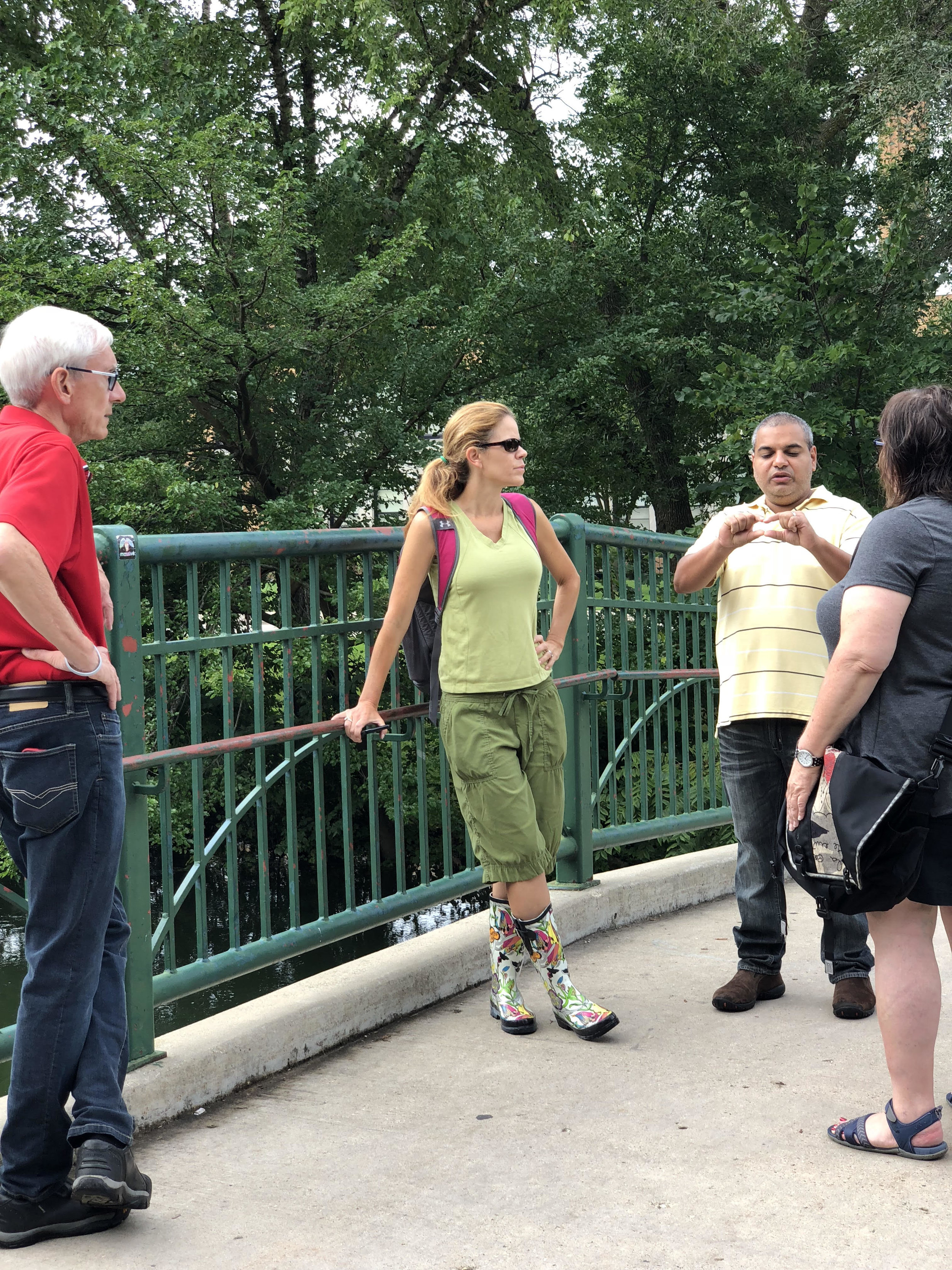 supervisor chawla, alder rummel, state rep taylor and superintendent evers survey water levels on the yahara river