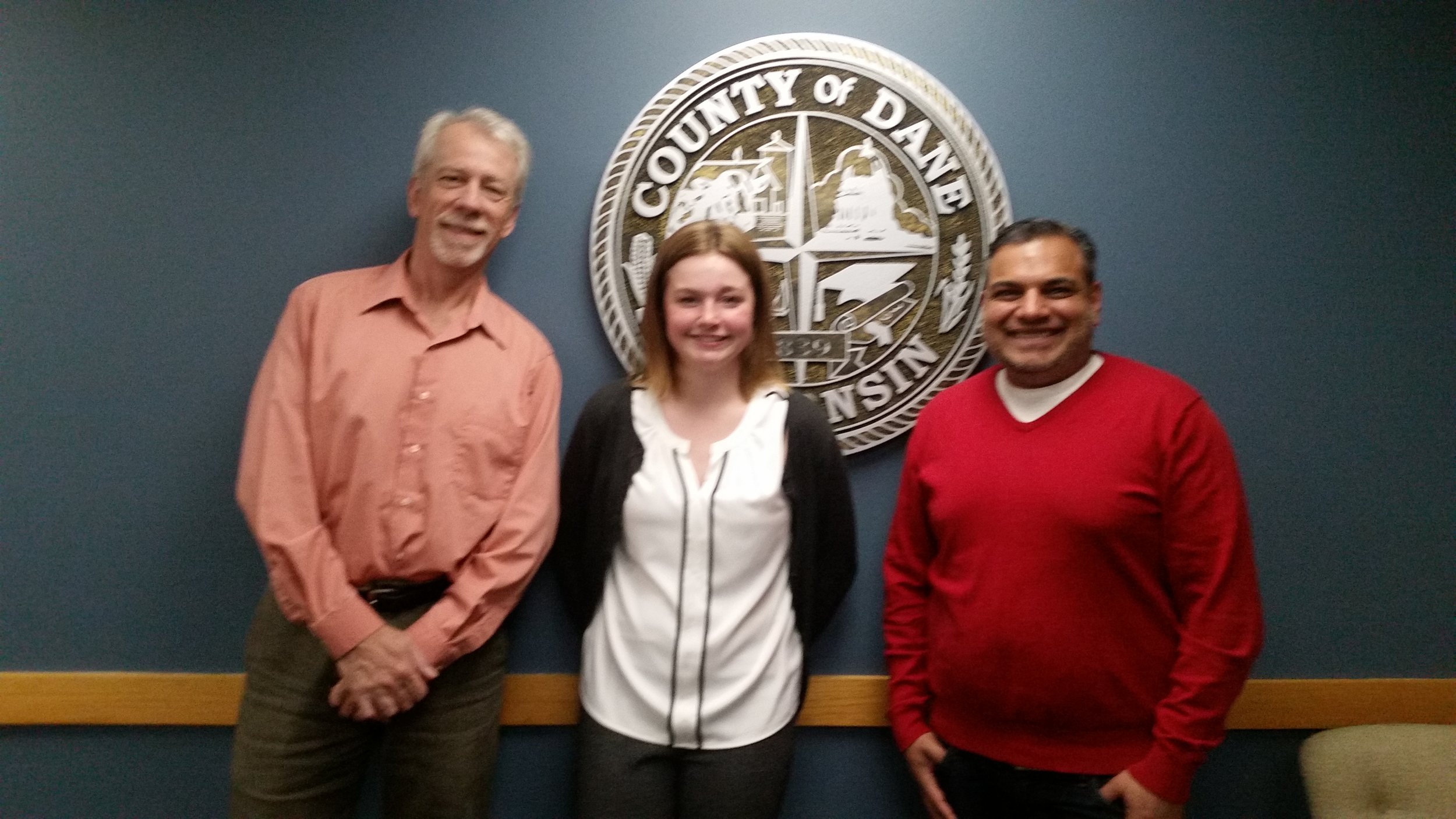 Keith, Lily and Yogesh snap a photo in front of the County Seal after a productive meeting.