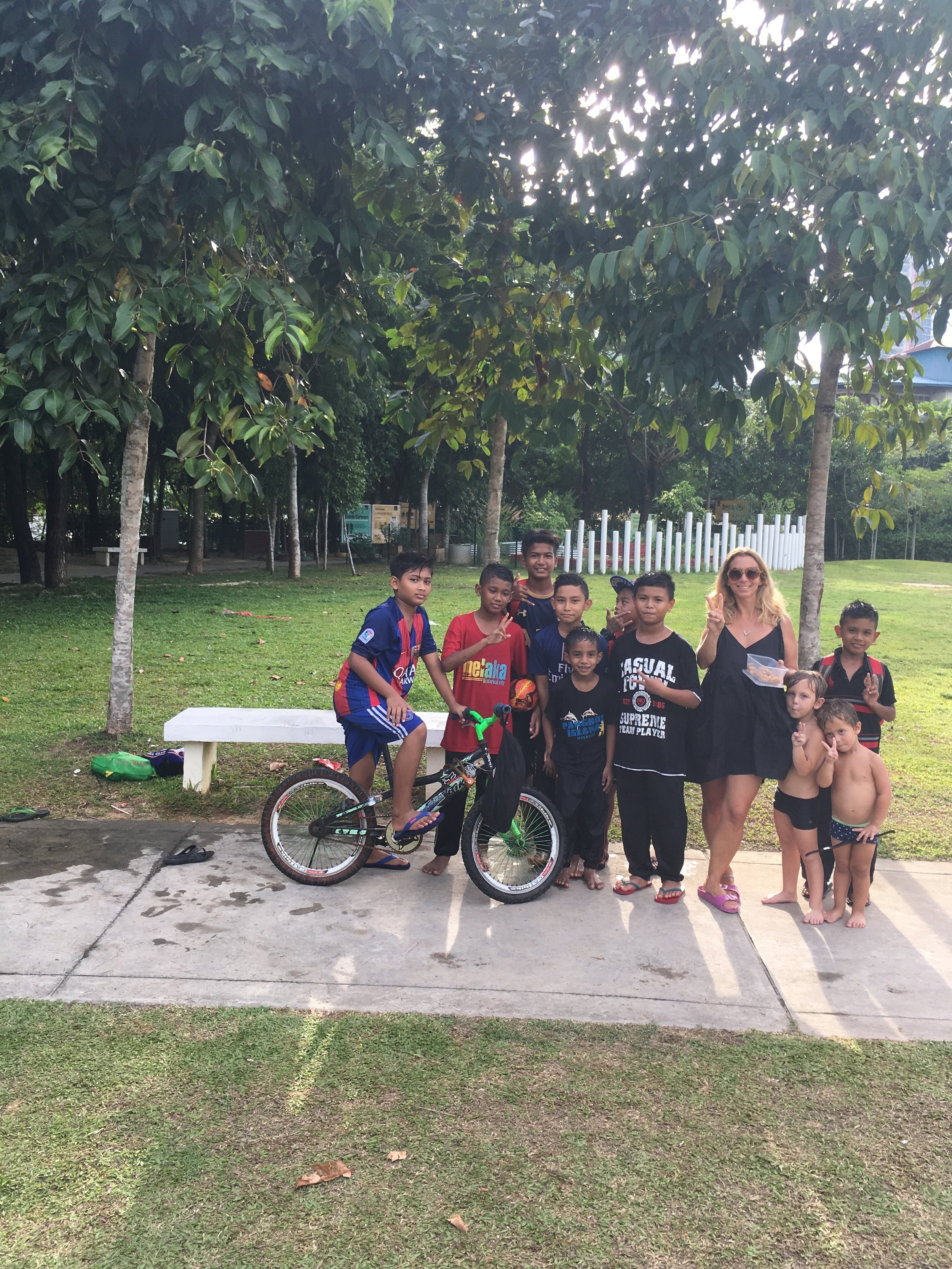In a park in Penang, Malaysia. The boys became friends with this group of children and one went home to look for cookies made by his mother, to share with us.