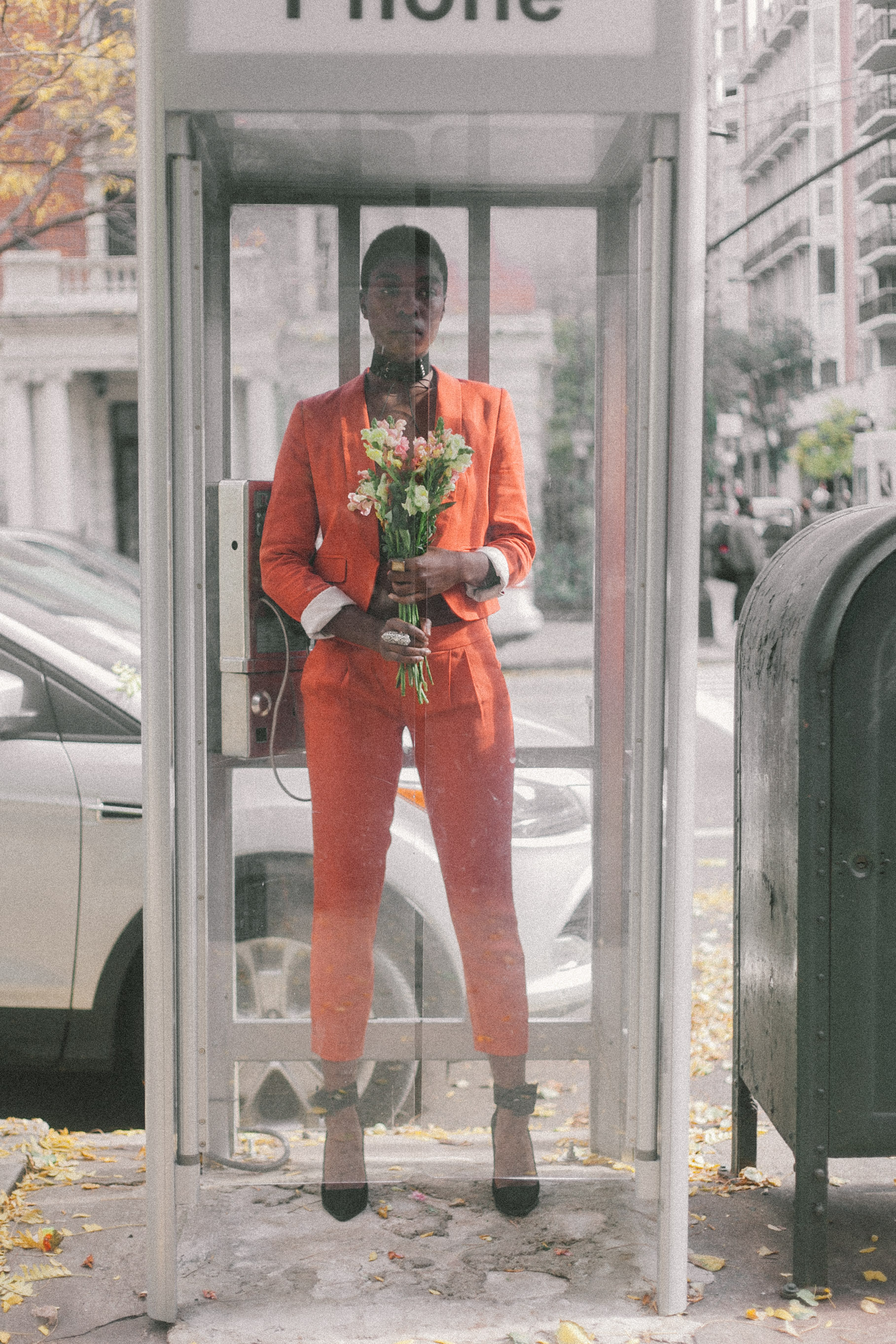 Creative Portrait Photography of a model standing in phone booth with flowers captured by Jarrod Anderson