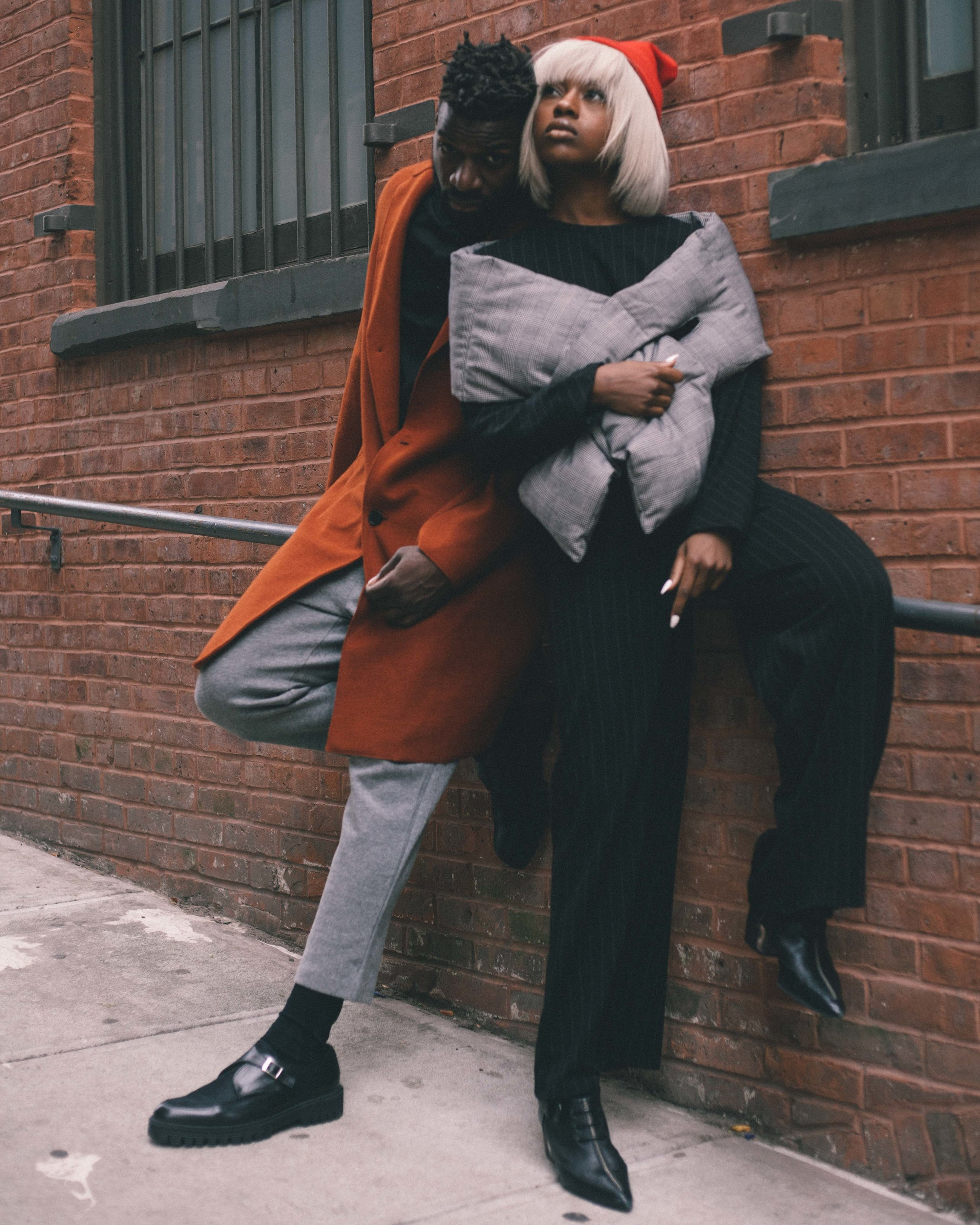 male model in orange jacket. female model in black pin suit. fashion photography captured by jarrod anderson in nyc.