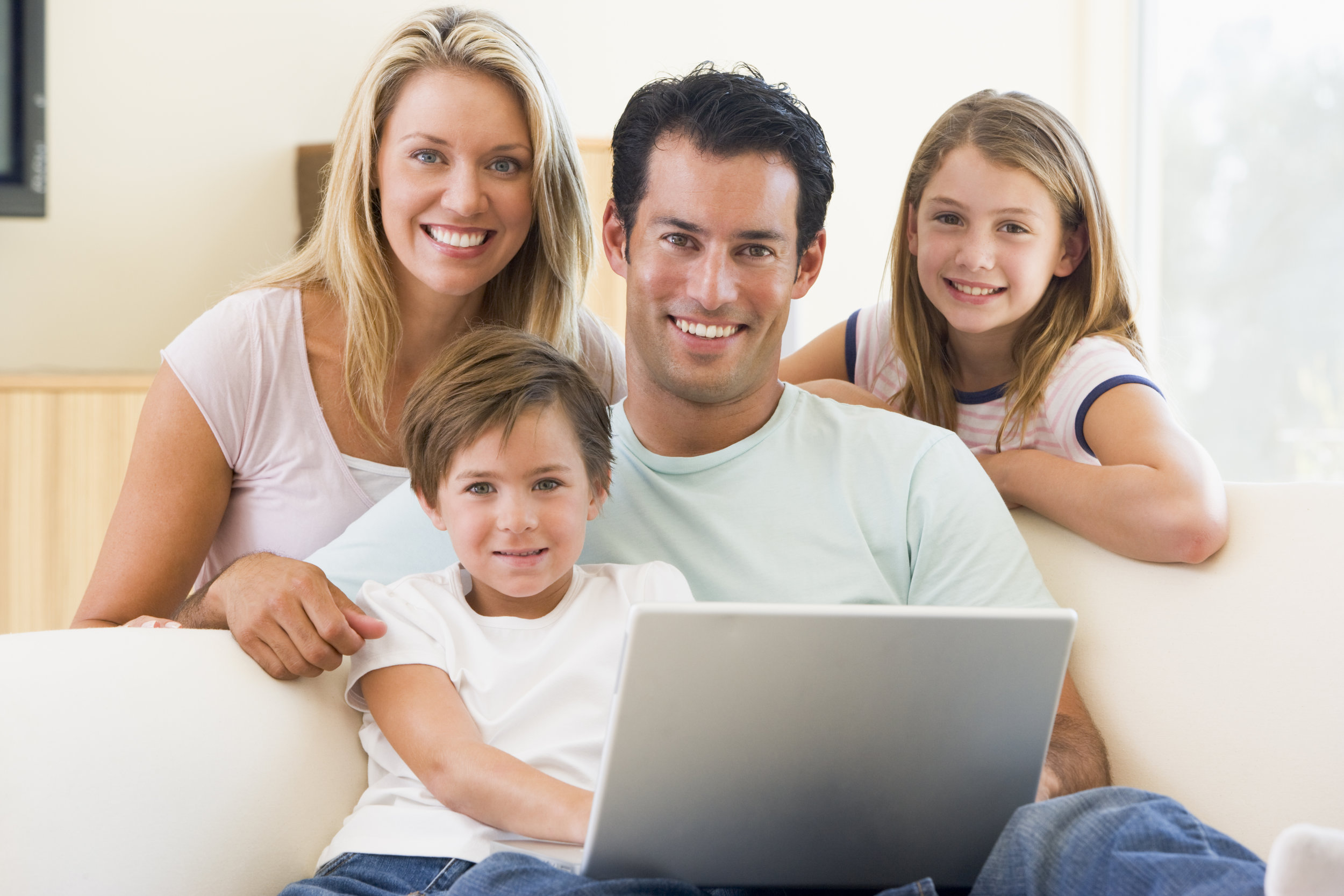 family-in-living-room-with-laptop-smiling_rFI642Cro.jpg