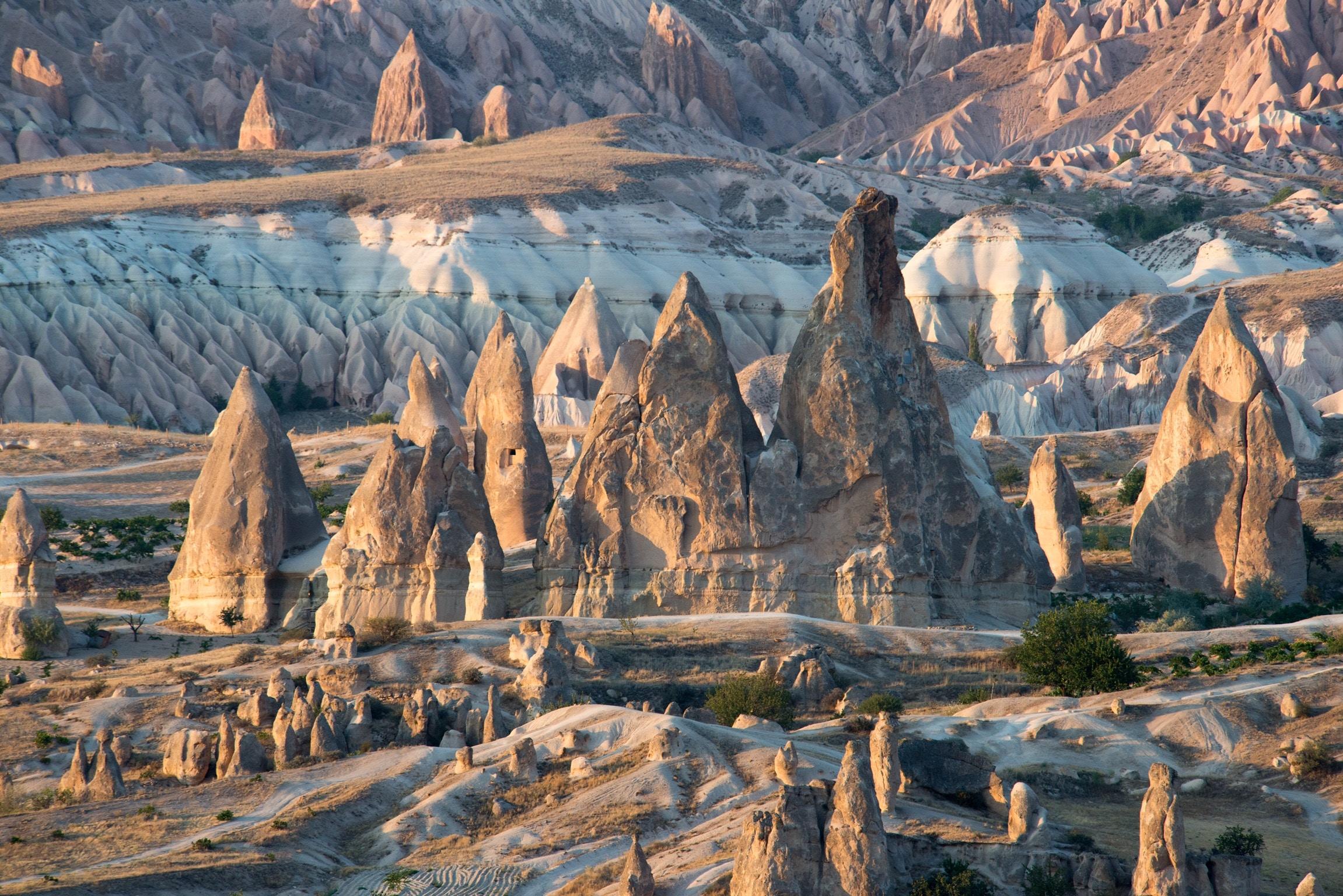 """卡帕多西亚以其童话般的斑点岩层而闻名:奇特的岩石构造、岩洞和半隐居人群的历史遗迹令人神往。这里起初是基督教徒躲避罗马迫害的避难处,公元4世纪,一群僧侣建立了卡帕多西亚的主要部分。经过长年风化水蚀之特殊景观,耸立着形状不一之岩石丘陵,在这些岩面上开凿了上千个洞窟,不少岩洞内还保存有许多湿壁画,为拜占庭艺术中反圣像崇拜后期之独特见证。卡帕多西亚独特的喀斯特地貌与月球表面类似,被称为""""地球上最像月球的地方""""。"""