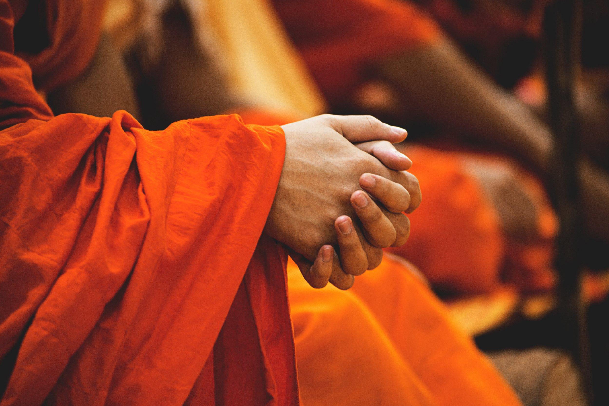 在佛像前双手紧握,用低沉的嗓音虔诚祷告