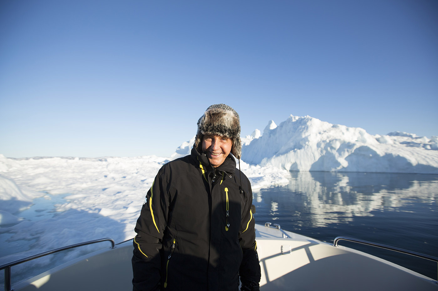 Geoffery Kent poses on boat infront of ice berg