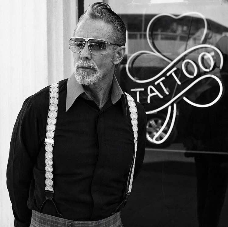 Mark Mahoney poses outside a tattoo parlor window