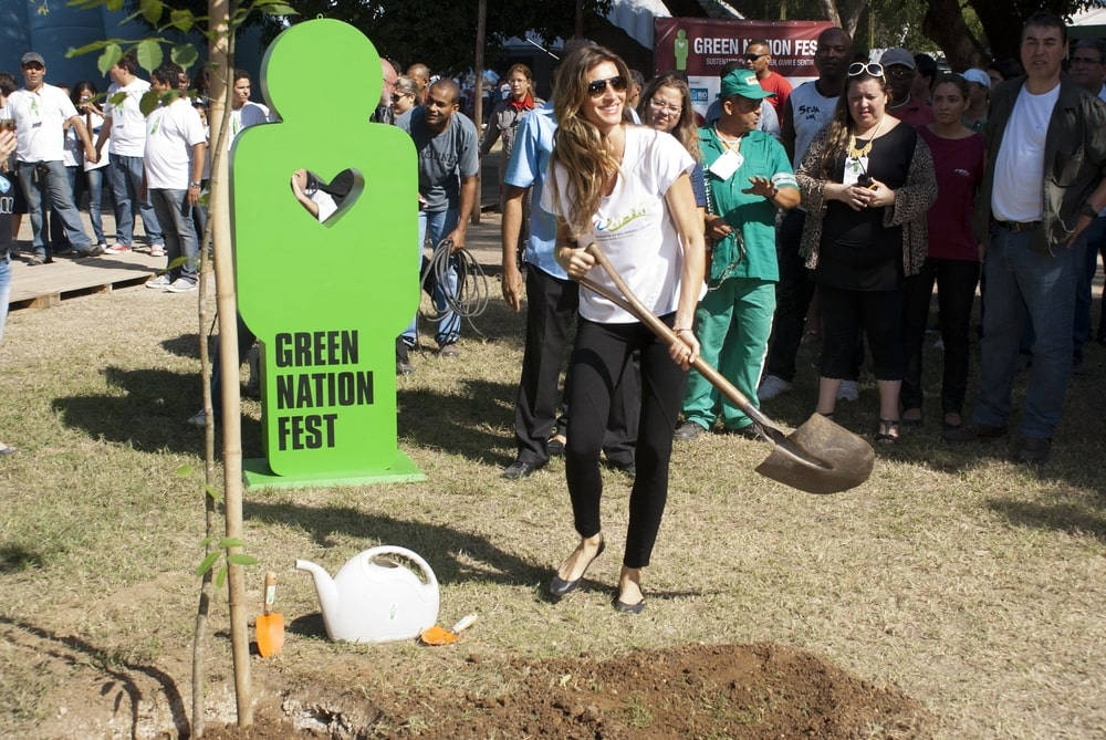 Gisele planting a tree at green nation fest
