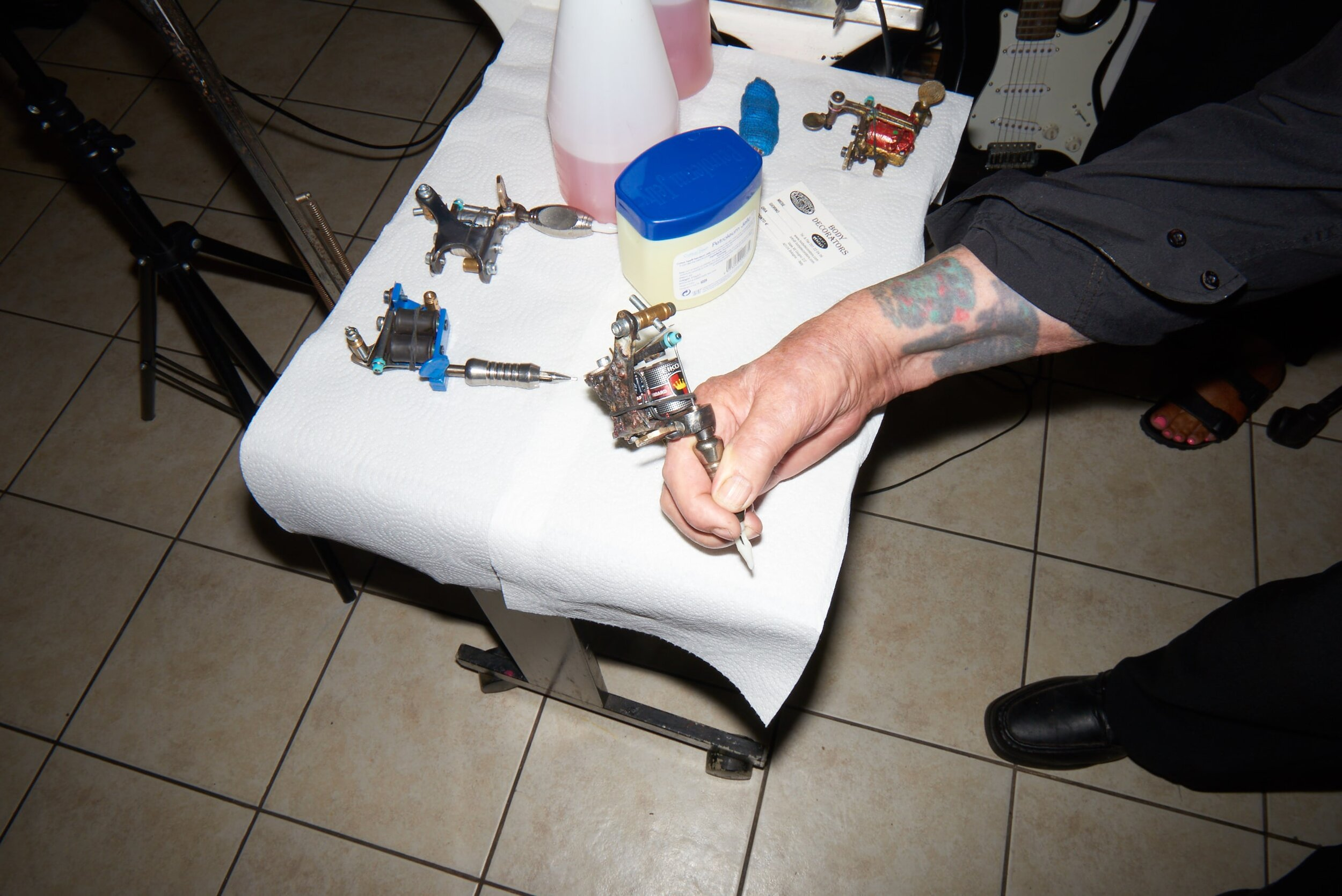 Doc Price's arm holding a tattoo needle resting on a table