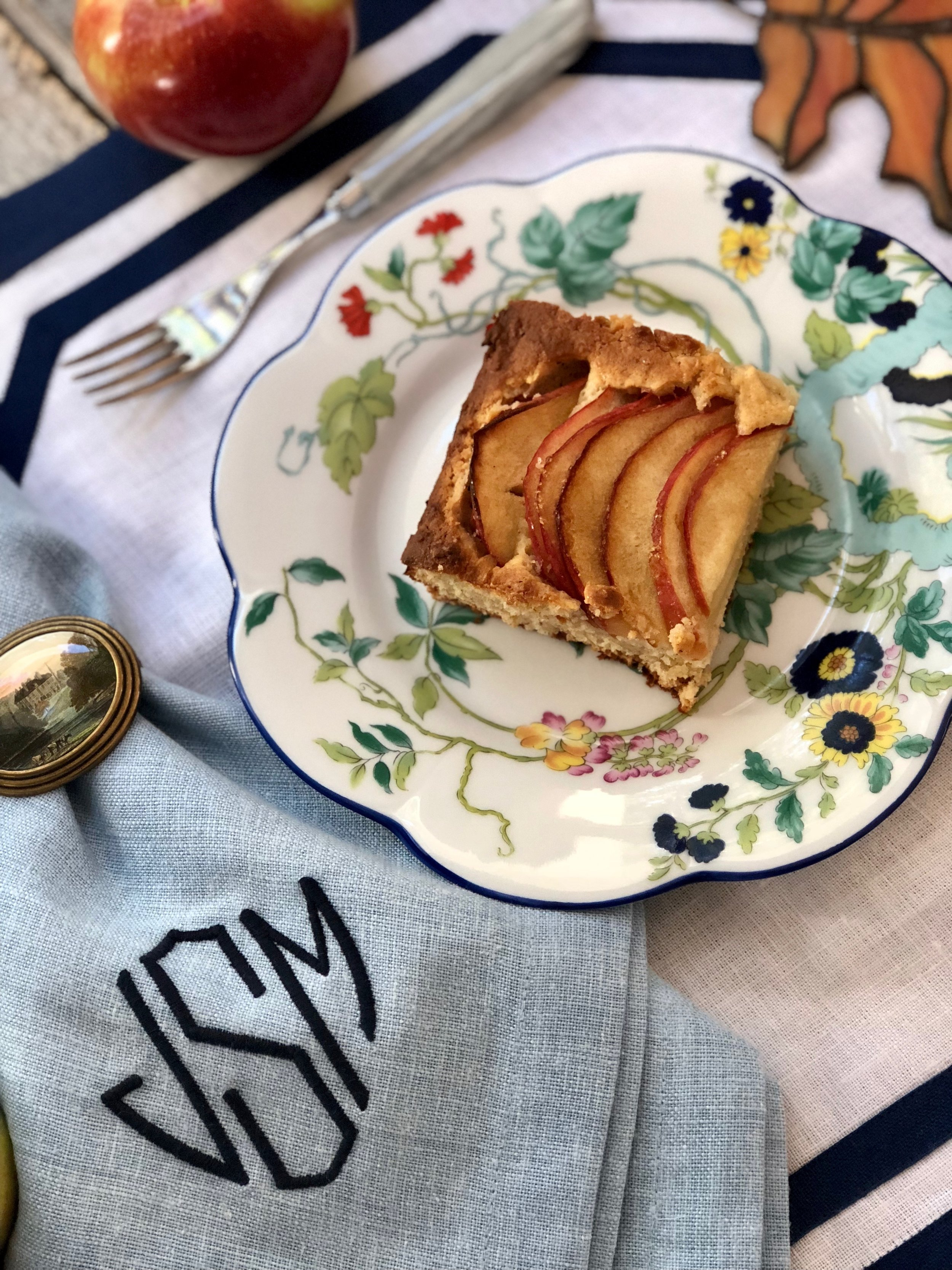 (L to R) Capdeco Flatware with faux marble handle (Dishwasher Safe), Matouk Chamant Napkins (available with custom monogram), Matouk Casual Couture Placemat, Royal Limoges Nymphea Paradise Bleu cake plate. Topped with a slice of Stacey's heavenly Apple Tray Bake.