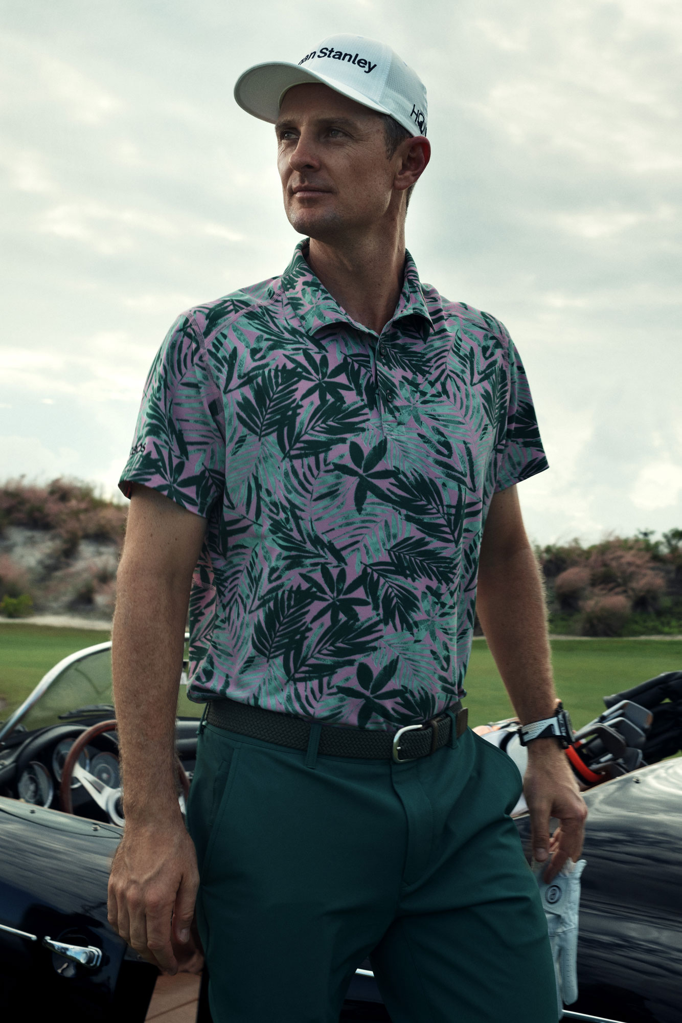 Justin wears the    M-Flex Flatiron Golf Polo (Pink Tropic Leaves)   , the    Highland Tour Pants (Deep Green   ), the    Clubhouse Stretch Belt (Grey)   .
