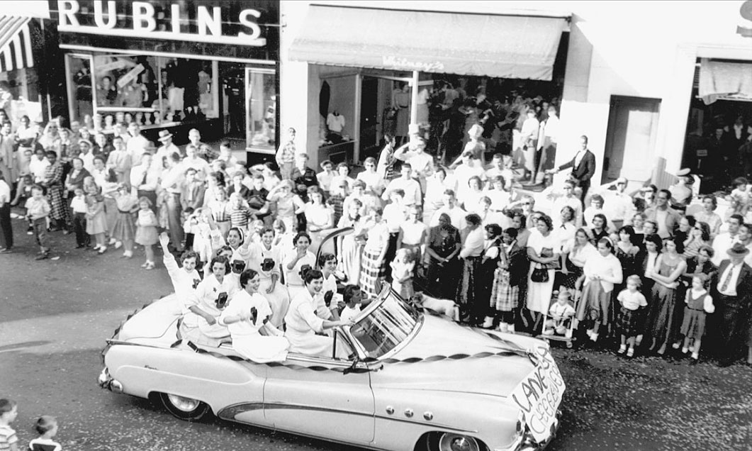 "Lane High School cheerleaders wave to the crowd as they cruise down the street.  (Courtesy Russell ""Rip"" Payne Collection / Albemarle Charlottesville Historical Society.)"
