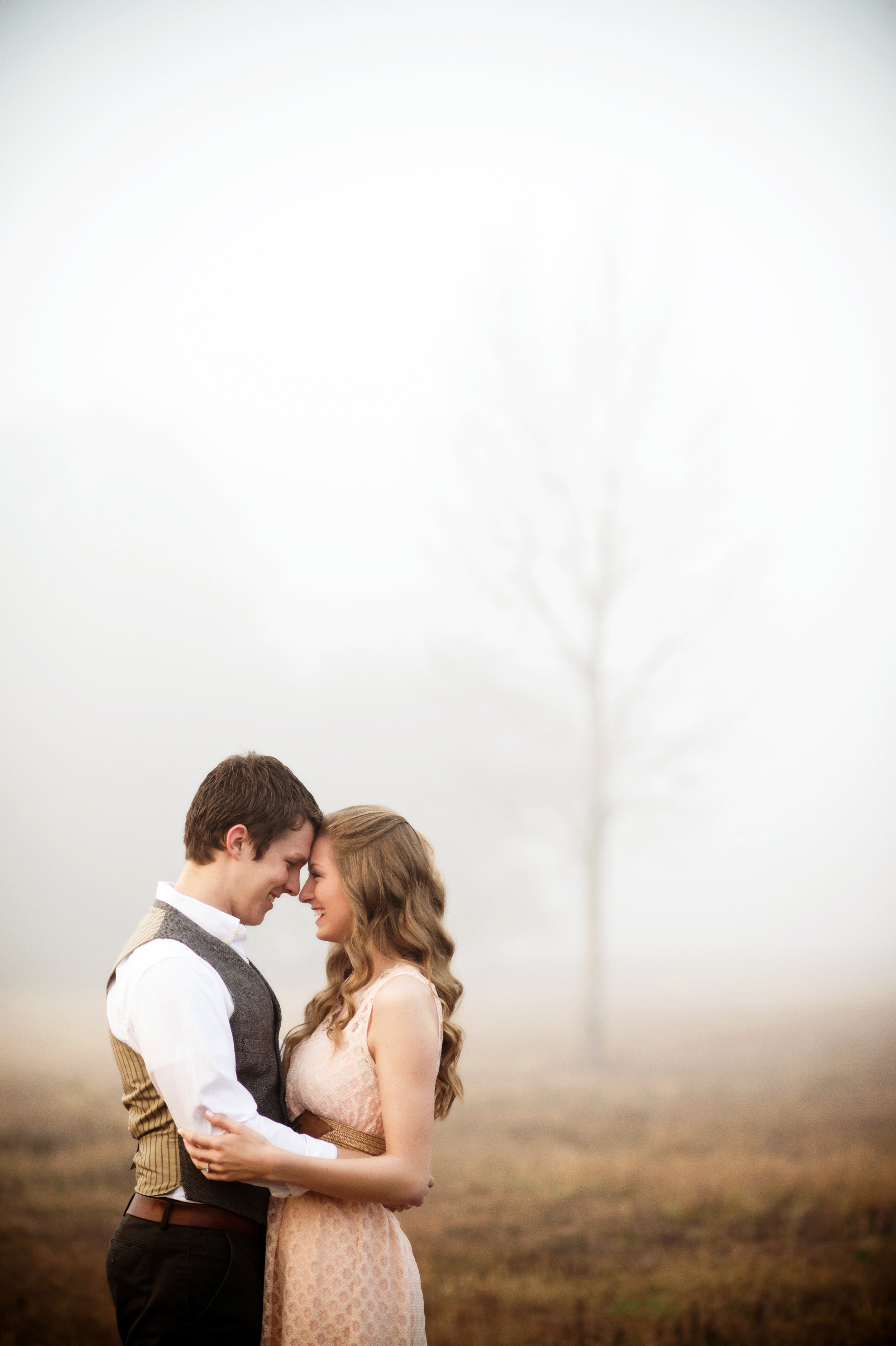Outdoor Engagement Photography in a field at Sunrise with trees