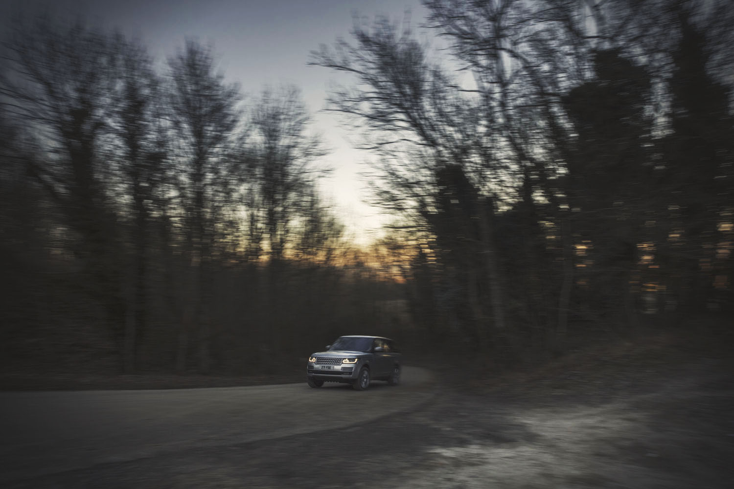 Sunset through woods Range Rover Commercial advertising automotive photography shoot.  off road in the Sussex for Land Rover. Packshot. Highlighting the Great British Outdoors, craftmanship, rural life and heritage brands. food photography still life.