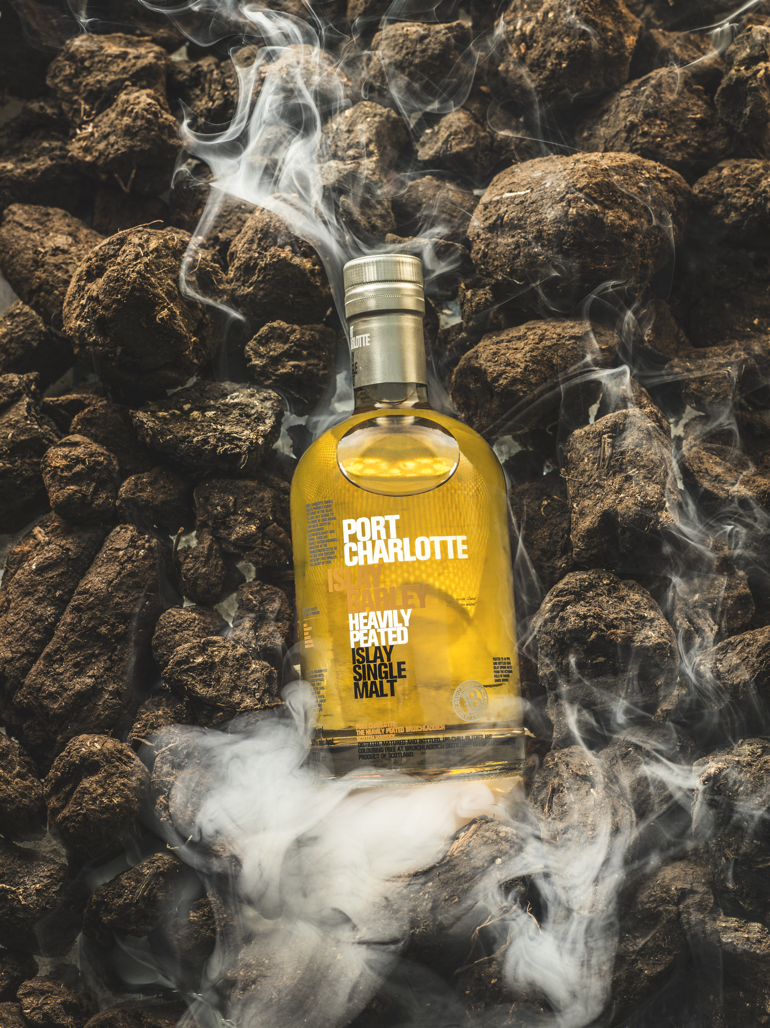 bruichladdich whisky on peat, still life drink shoot. advertising, packshot, striking clean modern imagery. lifestyle campaign images with atmosphere. Whisky, peat