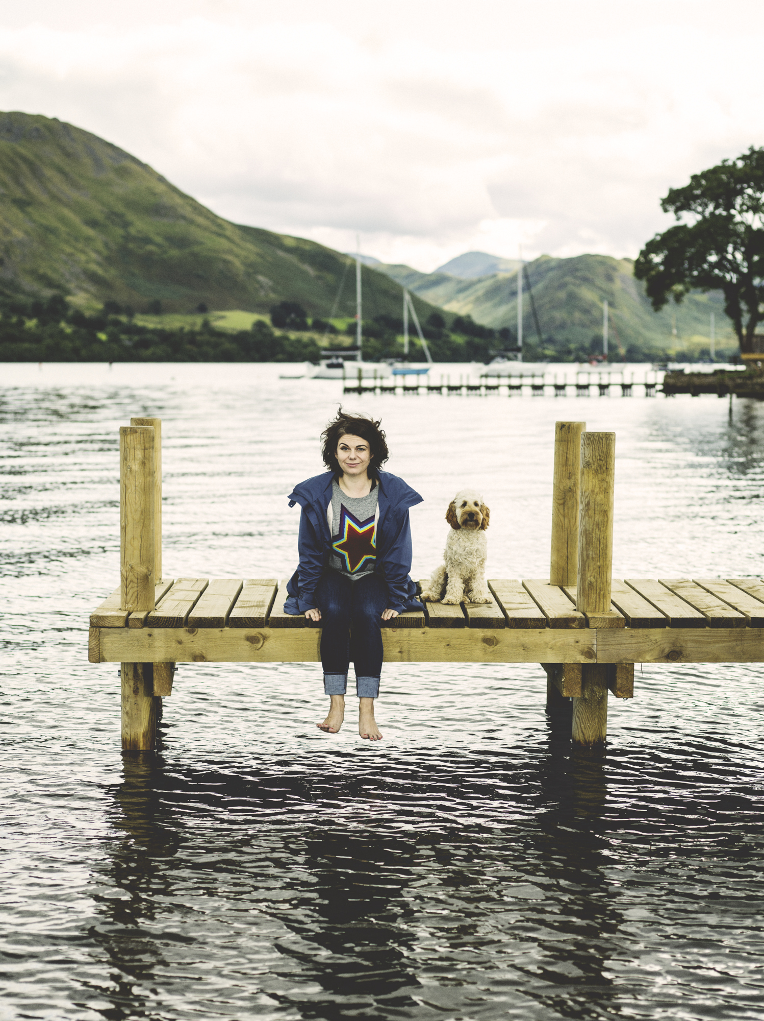 caitlin moran and dog sit on the pier of Another Place, the Lake, Ullswater for The Times.