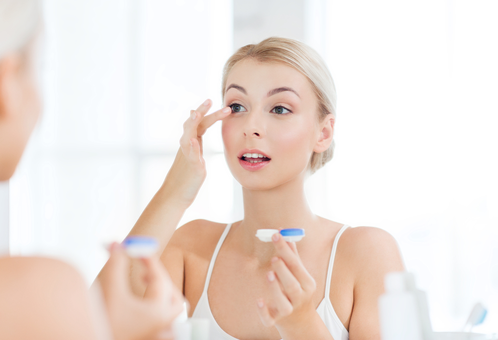 woman applying contact lense