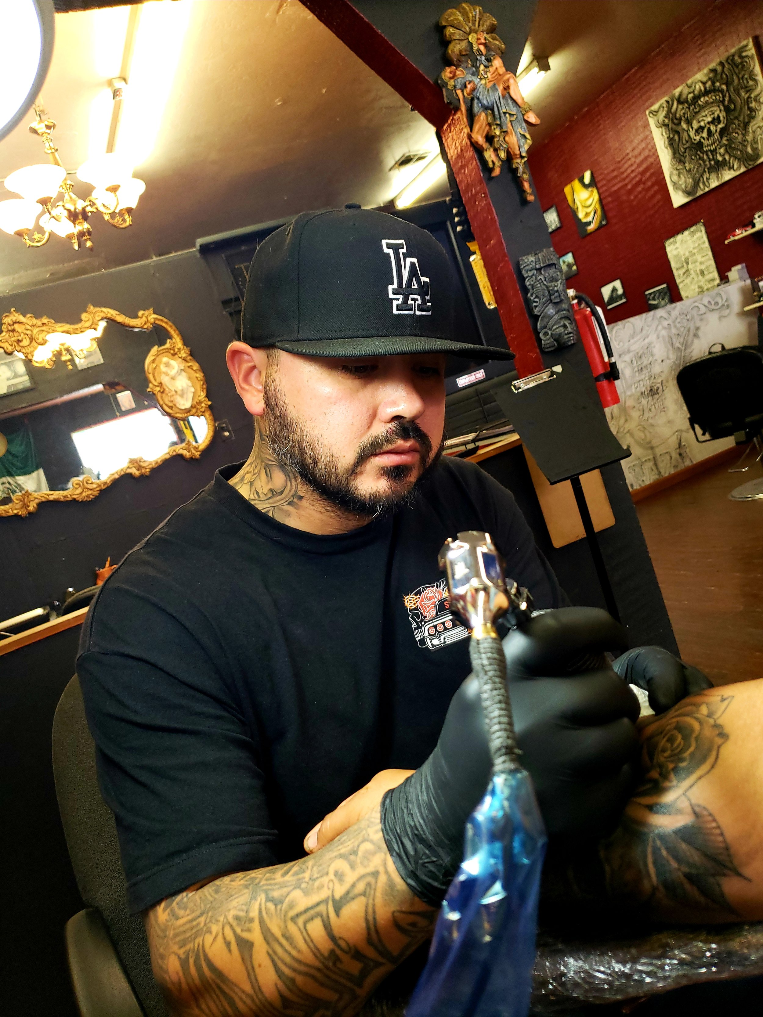 Mario Valdez - Mario was born and raised in the LA area and ended up settling down in the Central Valley. Art has always been a passion for him. After working a 9-5 for years, Mario got inspired by Bob Tyrell to pursue a career in tattooing. Since then he established himself in Tulare, CA at La Raza Tattoo. Specializing in fine line black and gray, cover ups and script. Click his picture to check out his work.