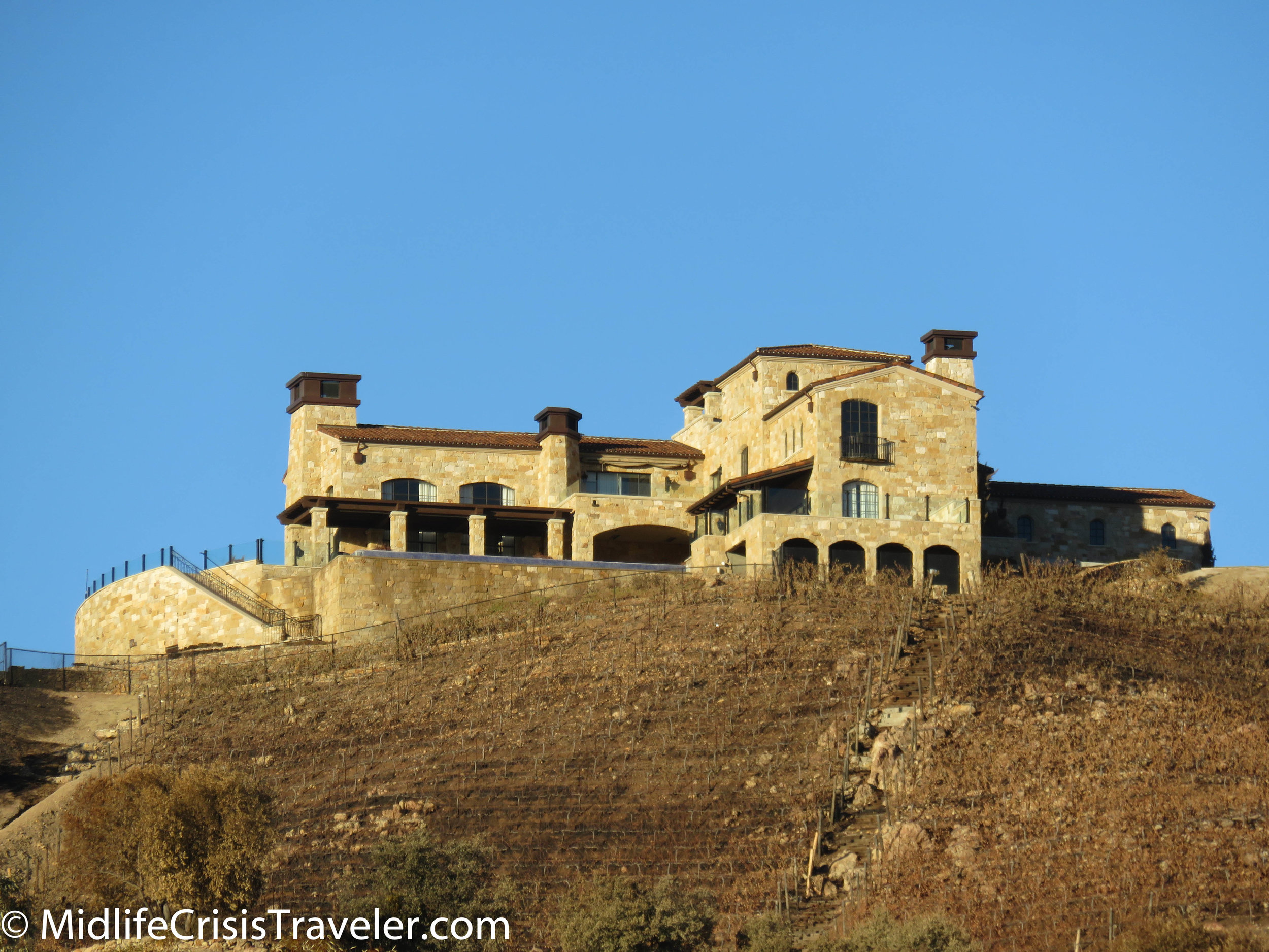 A stone mansion which survived the fires overlooks the mountains.