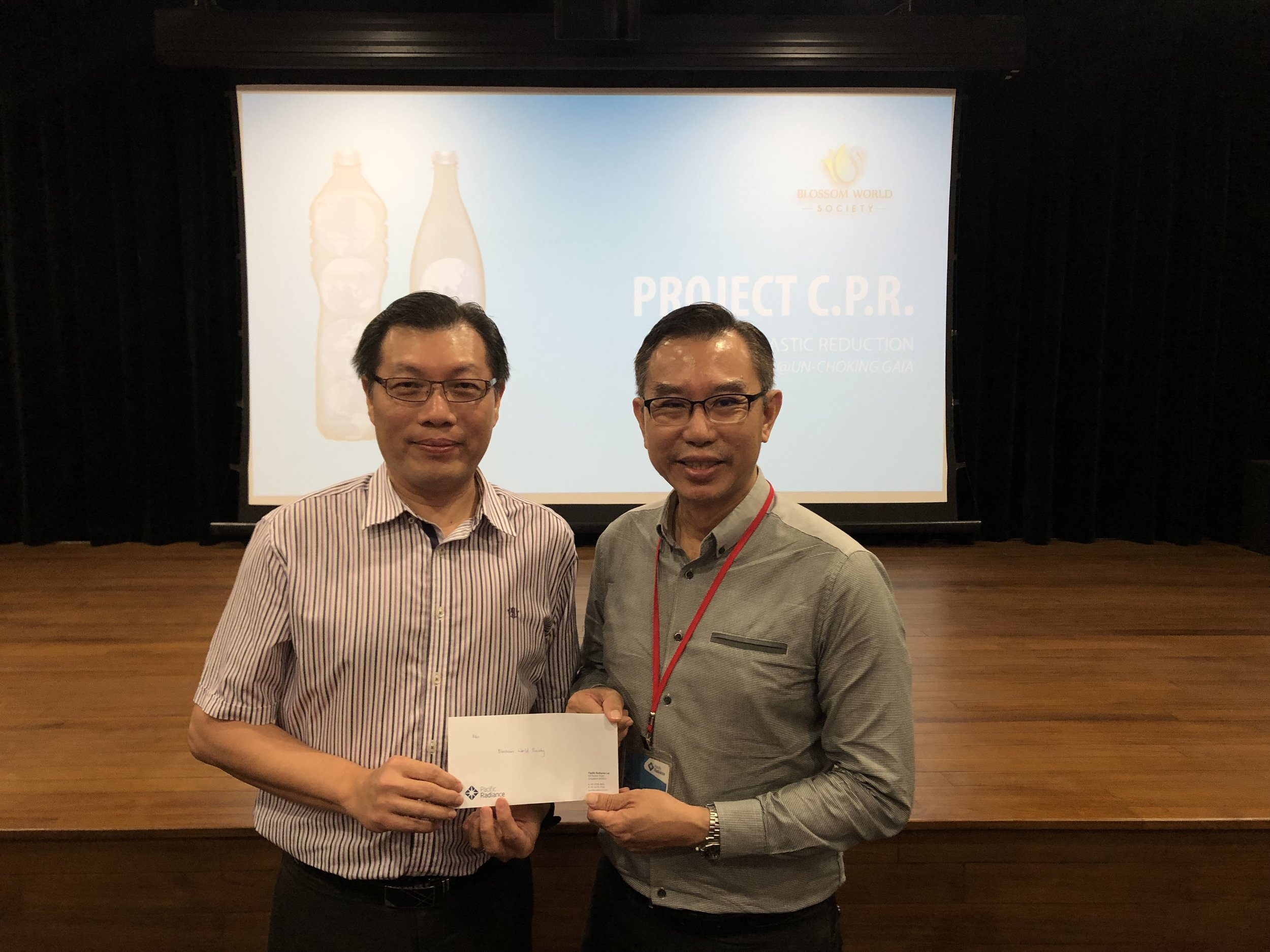 Presentation of a cheque, graciously by Pacific Radiance to Blossom World Society after the sharing done by Yu Ling.