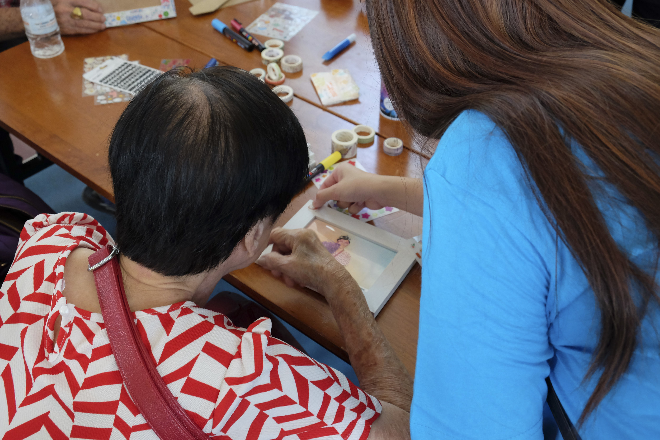 Moving on, we got the elderly to sit around the tables to start decorating photo frames for them to take home. Team CoLOVEful had stickers that ranged from food to cartoons, washi tapes, stars and googly eyes. The elderly were assisted by the volunteers to decorate their photo frame.  Before the event ended, food was served and the elderly had local sweet and savoury delicacies after long hours of having fun. Sweet delicacies from both Chinese and Malay race were included, savoury delicacies included our local favourites like curry puff, egg tarts and carrot cake sticks.