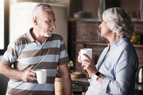 Older couple smiling and enjoying a cup of coffee after restorative prosthodontic dental treatment