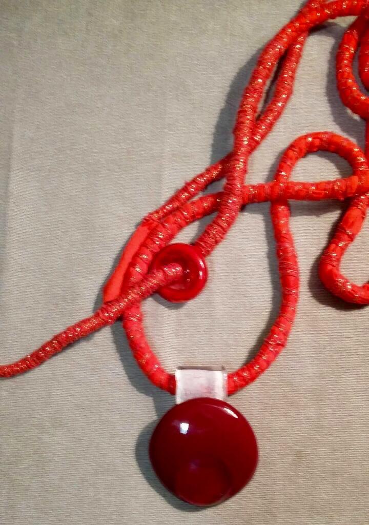 Medalha de copo de cristal vermelho quebrado com pedaços de garrafas cortados. Tecido e linha bordados.