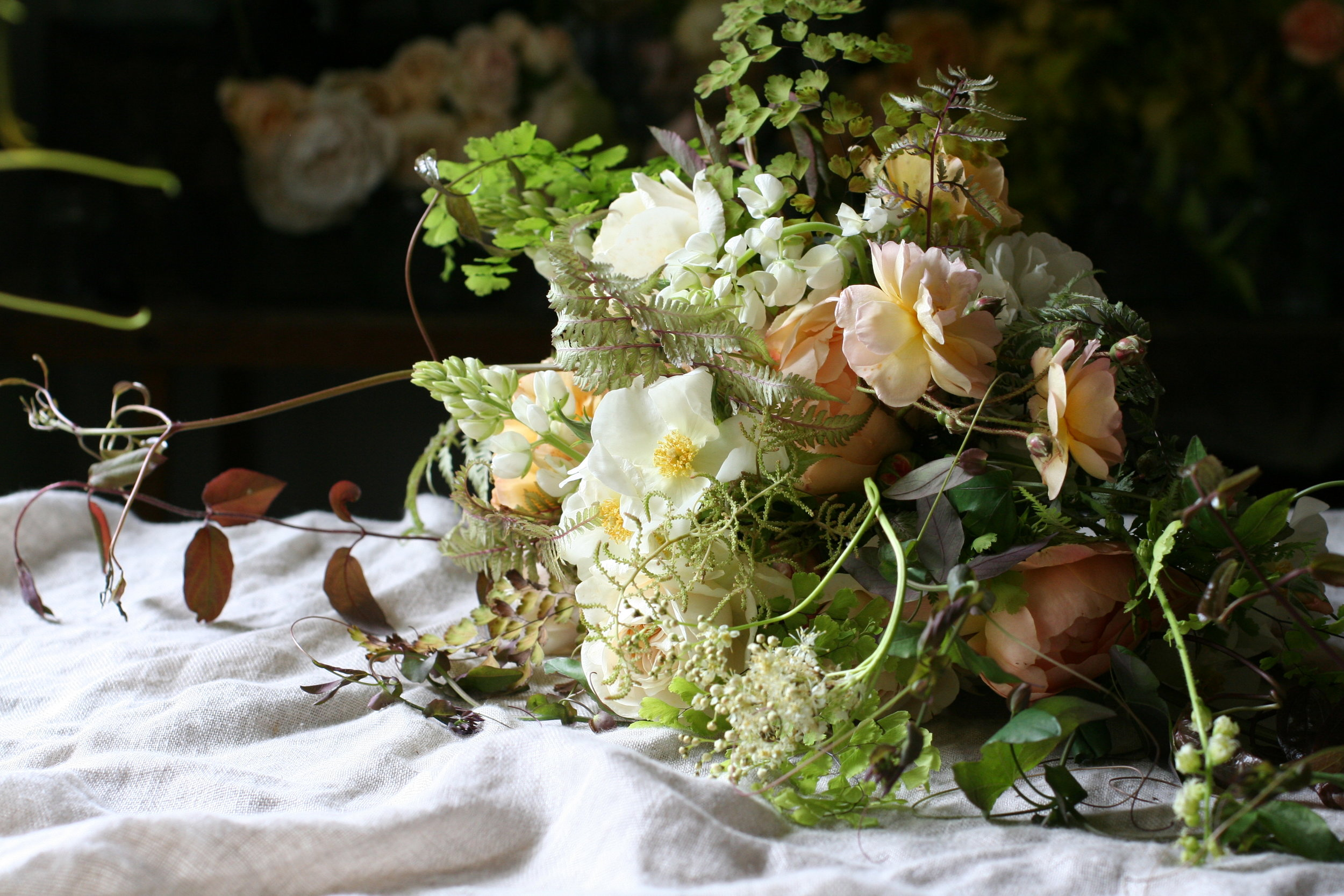 A wild and loose bouquet celebrating garden roses, lupins, japanese painted ferns and maidenhair fern.  Photo by Lucy