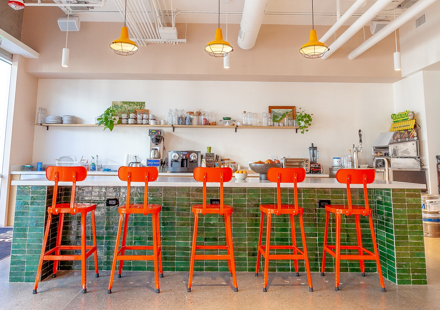 Orange powder-coated industrial style bar stools make a style + color statement at Lazy Dog Cafe's corporate headquarters. Furnishings by SOURCE Creative Office Interiors.