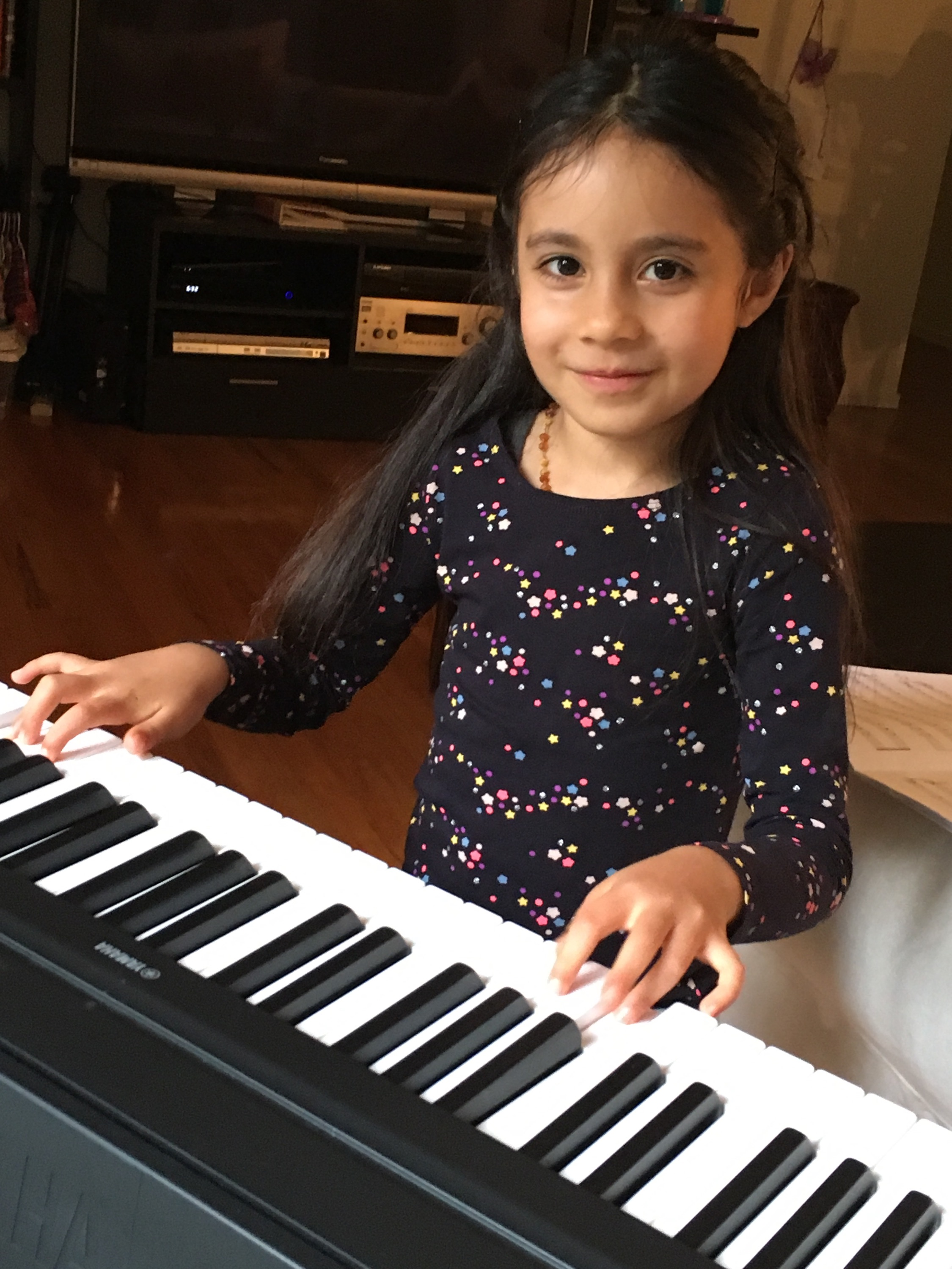 Alessandra practicing piano for her music lesson.