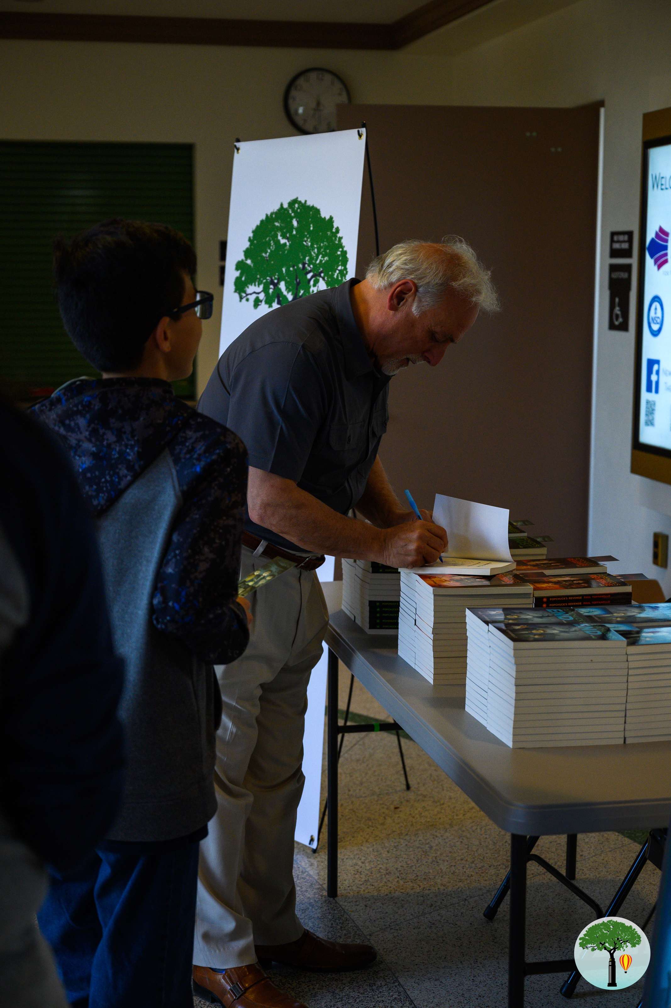 Paul Toffanello signs books for the audience members.