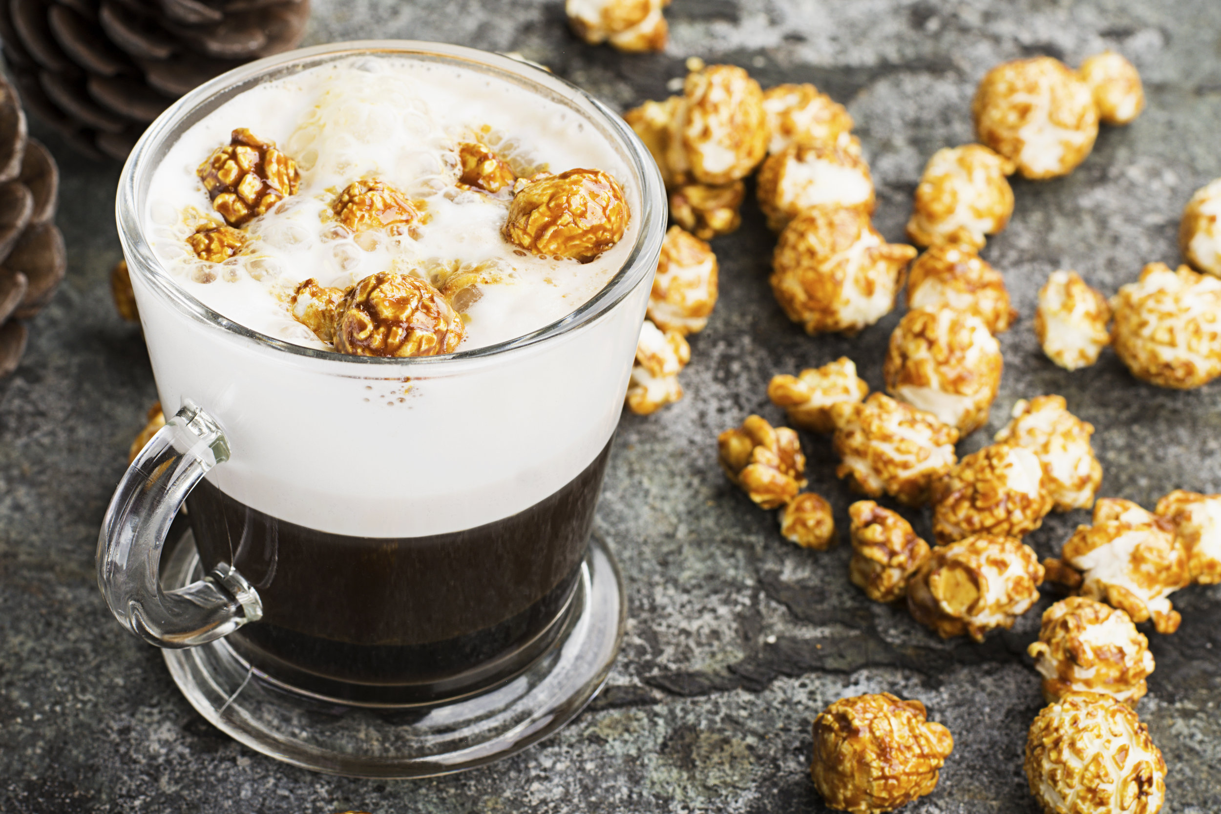 A-glass-of-mouth-watering-sweet-milk-coffee-with-a-creamy-foam-topped-with-caramel-crispy-popcorn-on-a-gray-stone-background.-Selective-focus.-842419862_4770x3180.jpeg
