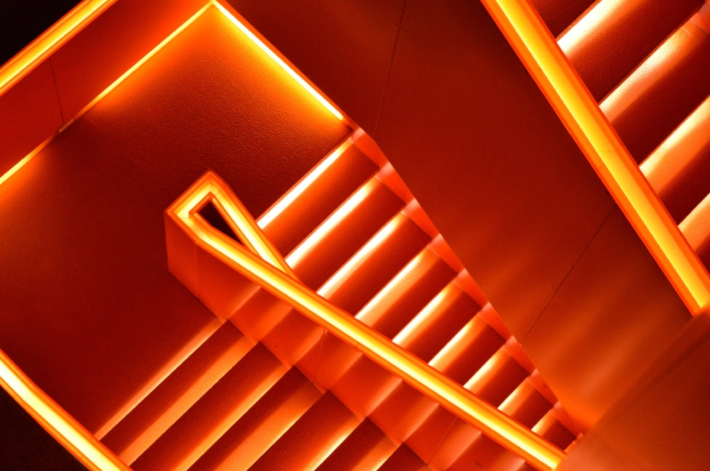 An orange staircase is an example of bold use of color in interior architecture. Photo by Gabriel Izgi.