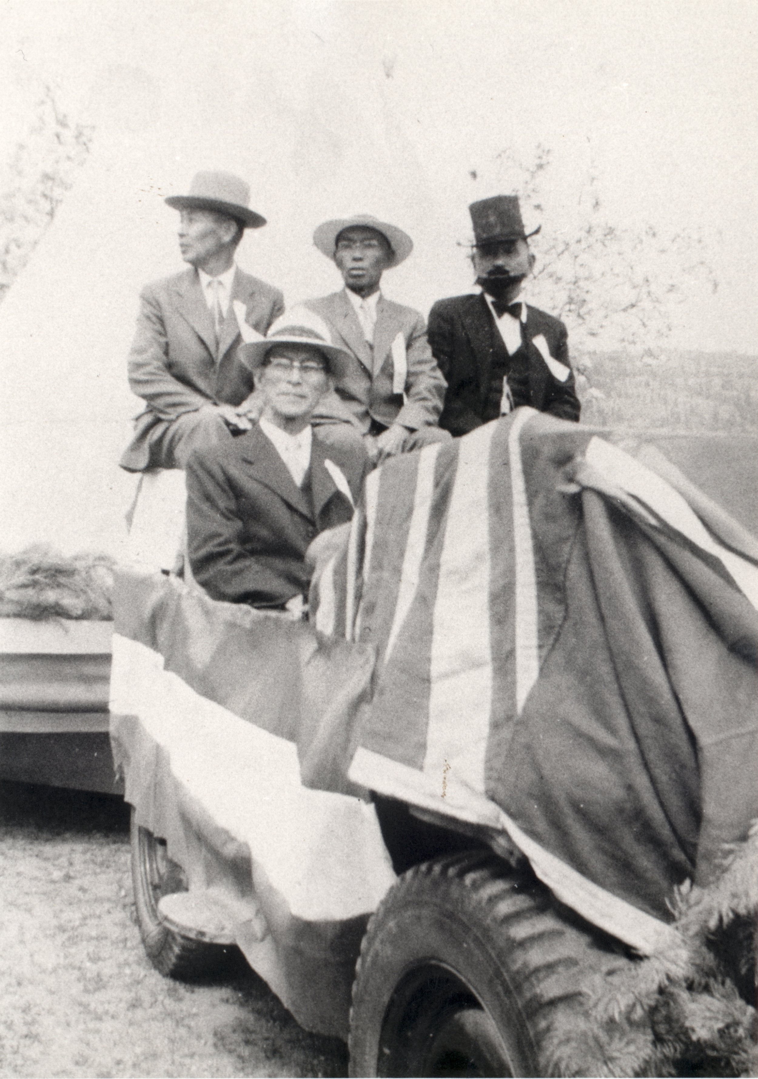 Kichinojo (Jack) Imayoshi, Mac Kuroda, Tom Kato, and Kew Kita (at front) sitting in decorated car that is pulling the Japanese float for the Golden Jubilee parade in 1956.