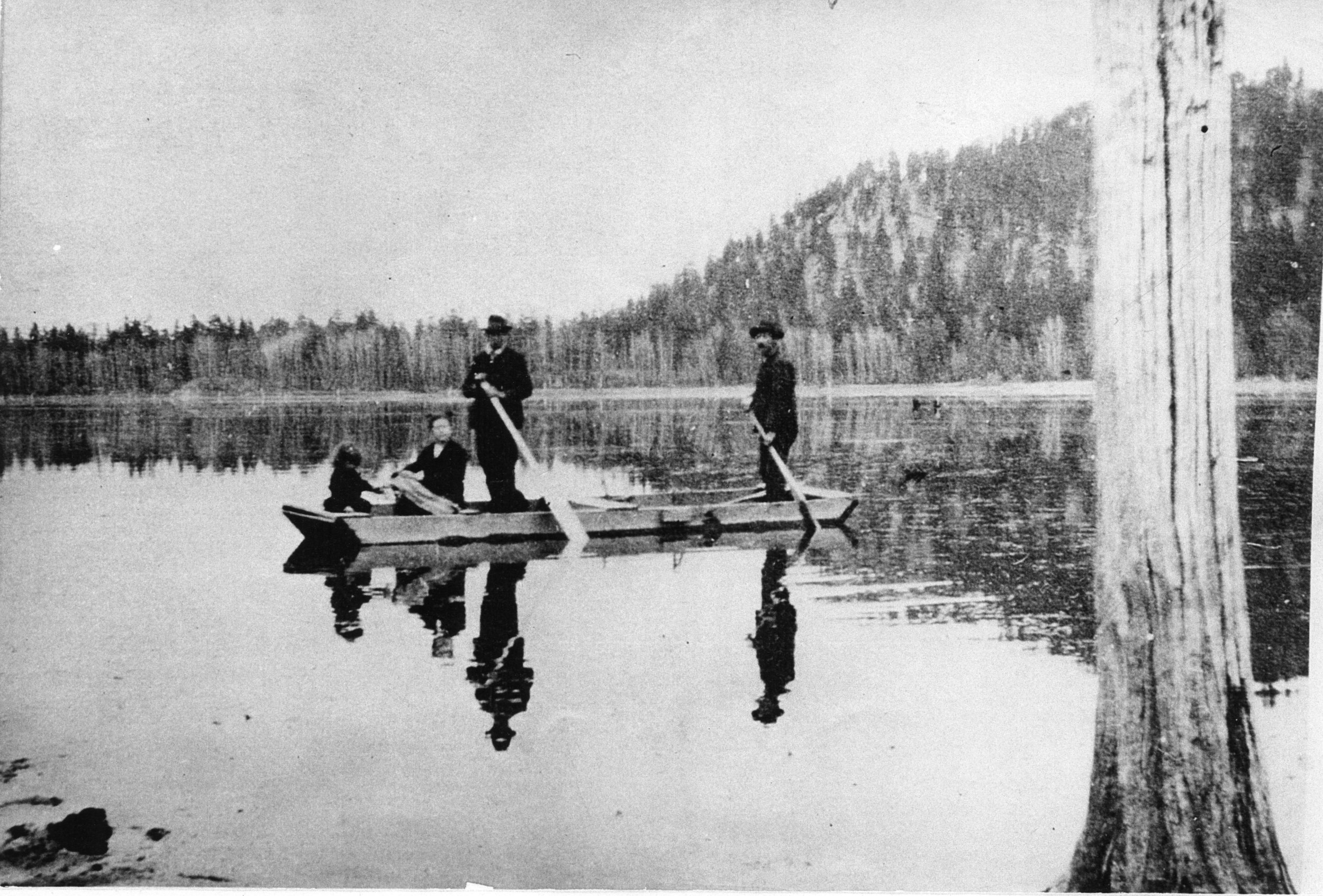Left to right: Linnie Munro (Hale), Mrs. Findlay Munro, Findlay Munro, and Philip Munro paddling a flat bottom boat on Fish Lake.