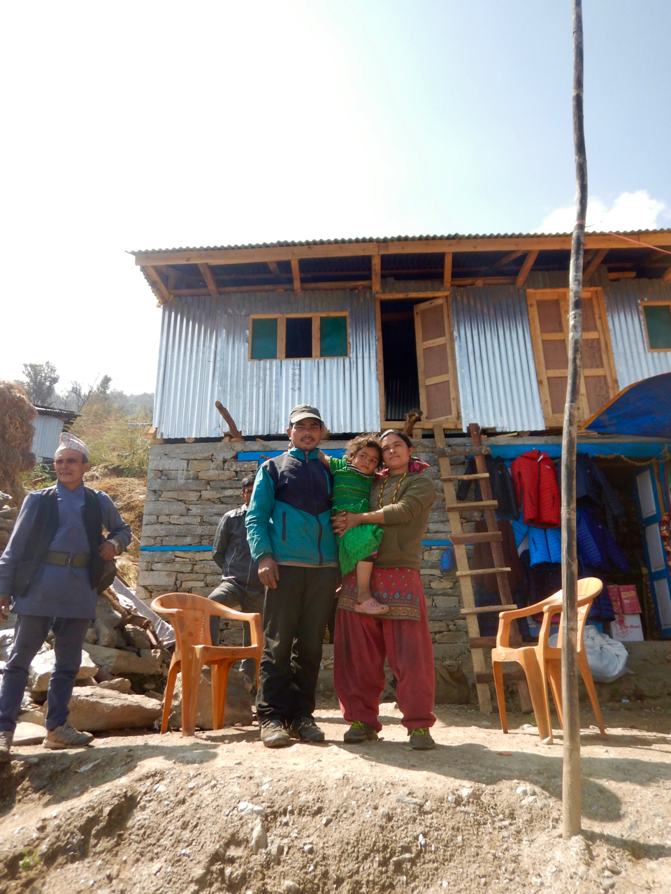 Family in front of house with 2 shops.