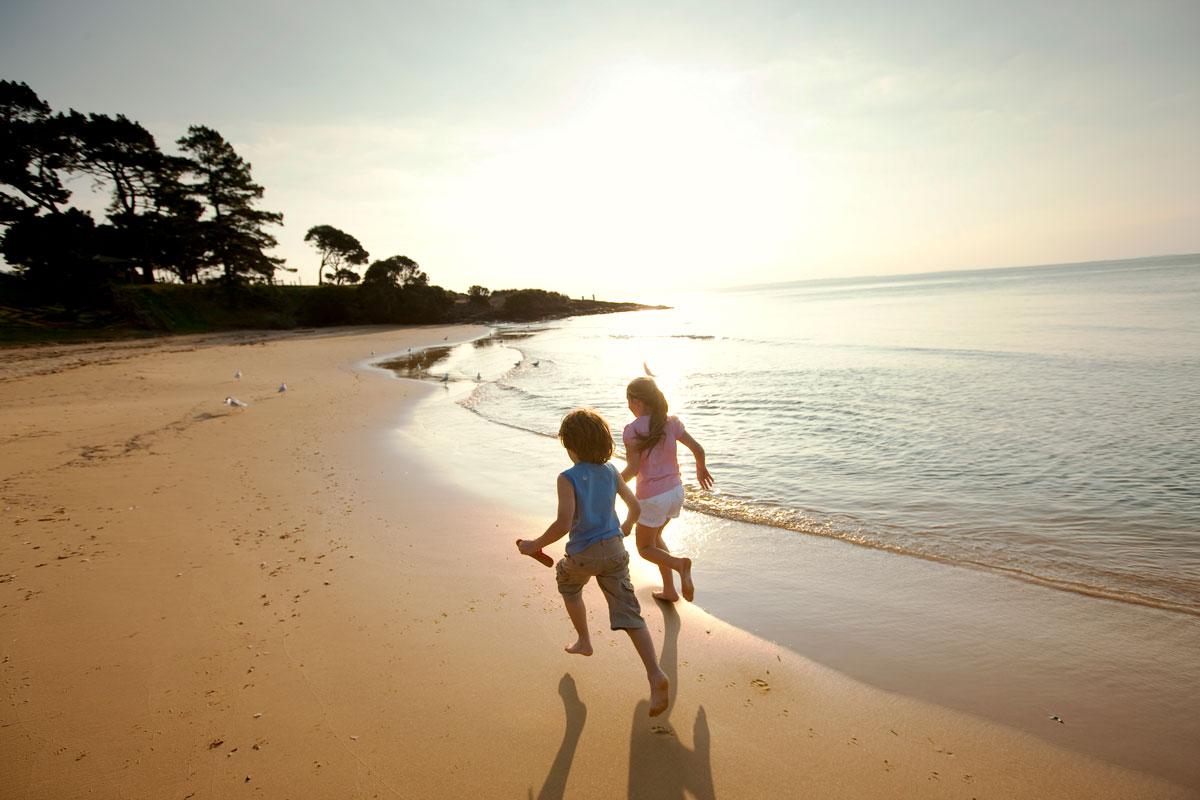 Kids running along the beach on Phillip Island