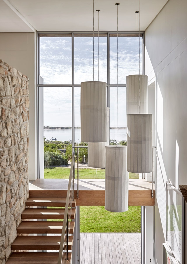 The wonderful play of light in the double-volume entrance hall is enhanced by the spaces between the floating wooden treads and the floor-to-ceiling glazing on the lagoon side. A floating montage of paper and bamboo pendant lights adds to the airiness of this space.