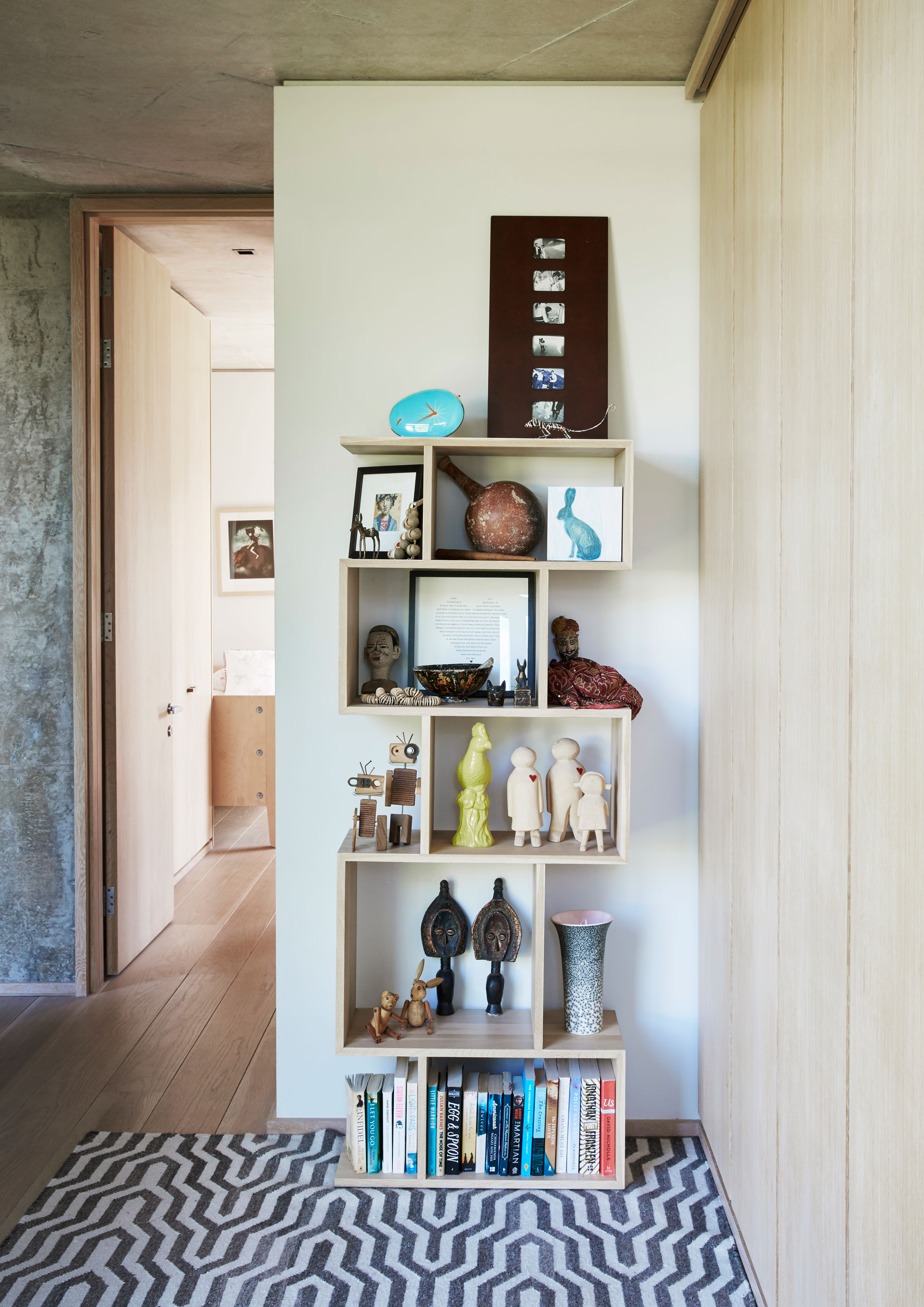 This bookshelf in the bedroom wing!&s passage serves to display some of Matt!&s collection of artefacts collected over two decades of backpacking through Africa, Asia, India and South America, interspersed with more recent finds upon which the couple more easily agree.