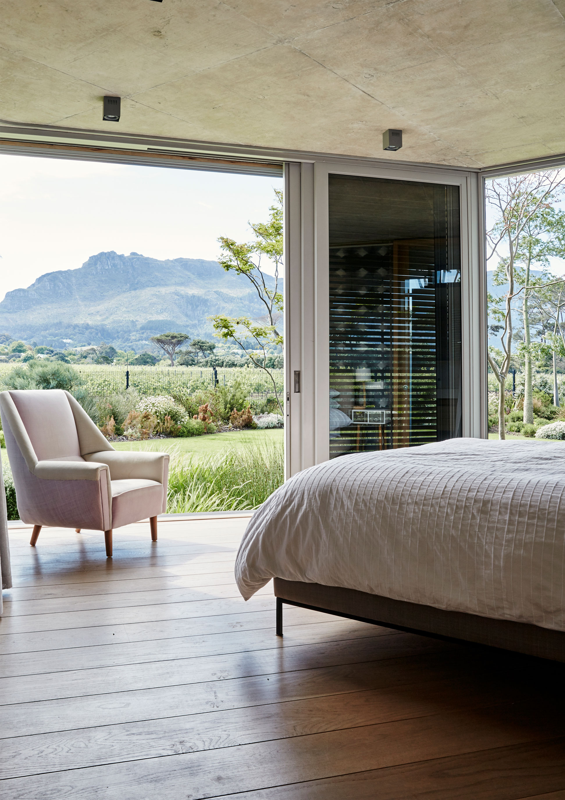 The master bedroom at the end of the bedroom wing has spectacular views of the garden, over the vineyards and to the Table Mountain range beyond. The angled, stepped formation of the rooms makes it possible for them each to have a north- and west-facing aspect. While the floor-to-ceiling glass sliding doors enable the views, the necessary privacy is created with sliding cedar screens. There are no ceilings in the bedrooms $ع they feature raw off-shutter concrete. The anthropomorphic Sitting Lamp is by Graeme Bettles. 