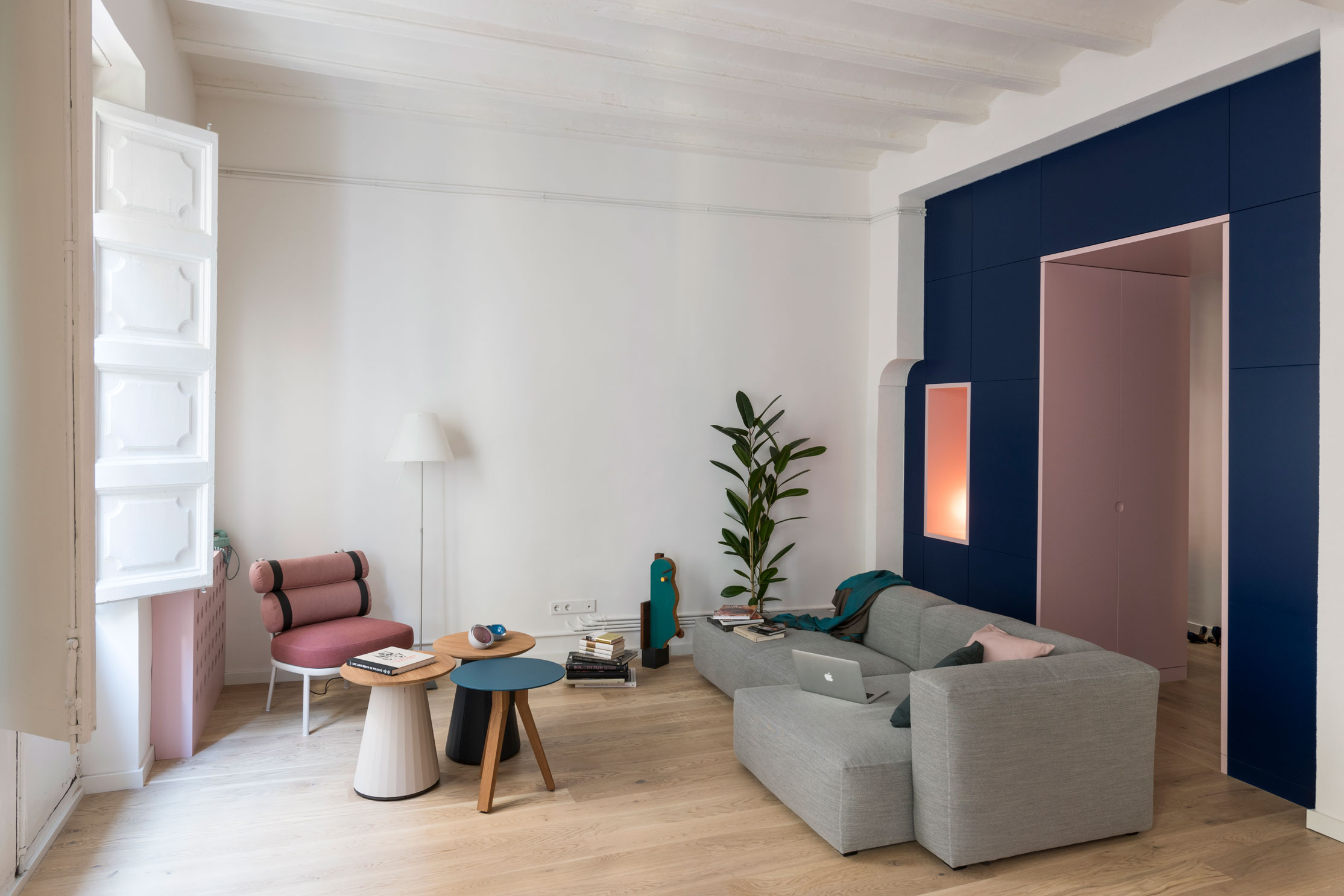 The living area is fitted with carefully chosen furniture: a Mags sofa by HAY, accompanied by a Roll Club Chair by Kettal; of the same brand are the side tables Cala and Vieques. A classic Costanza lamp by Luceplan and a wooden sculpture by OWL complete the sitting room.