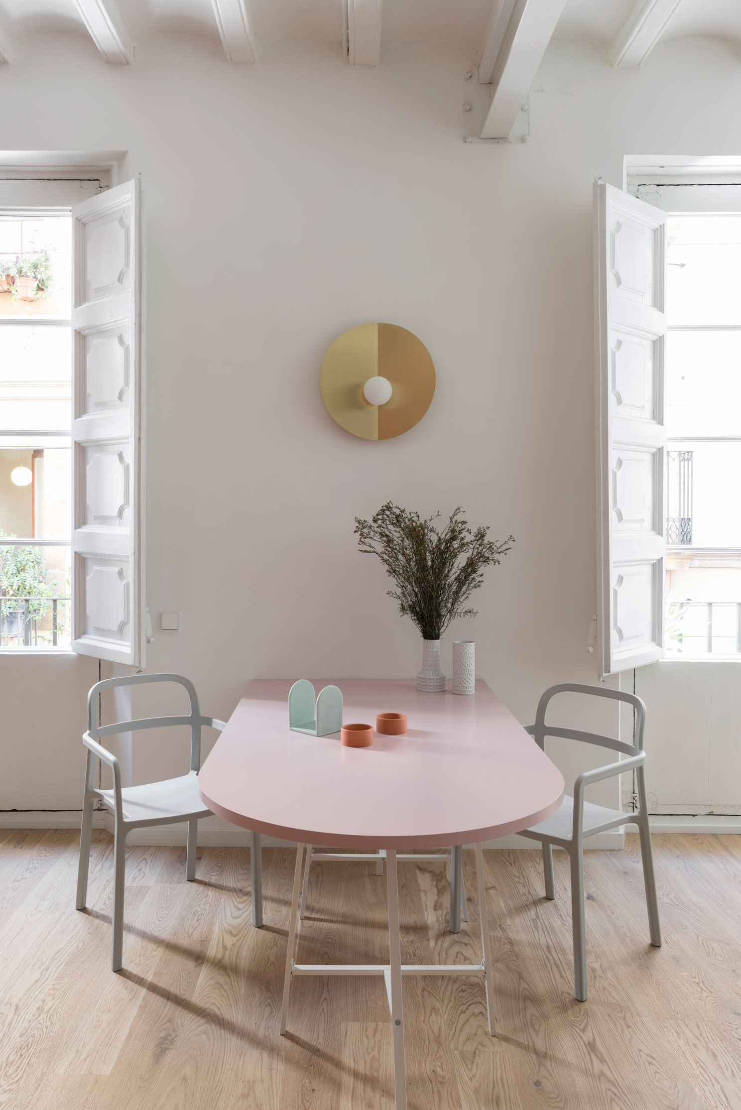 Between the two big windows, the golden disc of a Fold Lamp presides over the dining area. Designed by CaSA expressly for this project, the light is produced by Barcelona brand Metalware.  Below it, a wide table lacquered in pink, is flanked by Ypperlig chairs by HAY for IKEA.