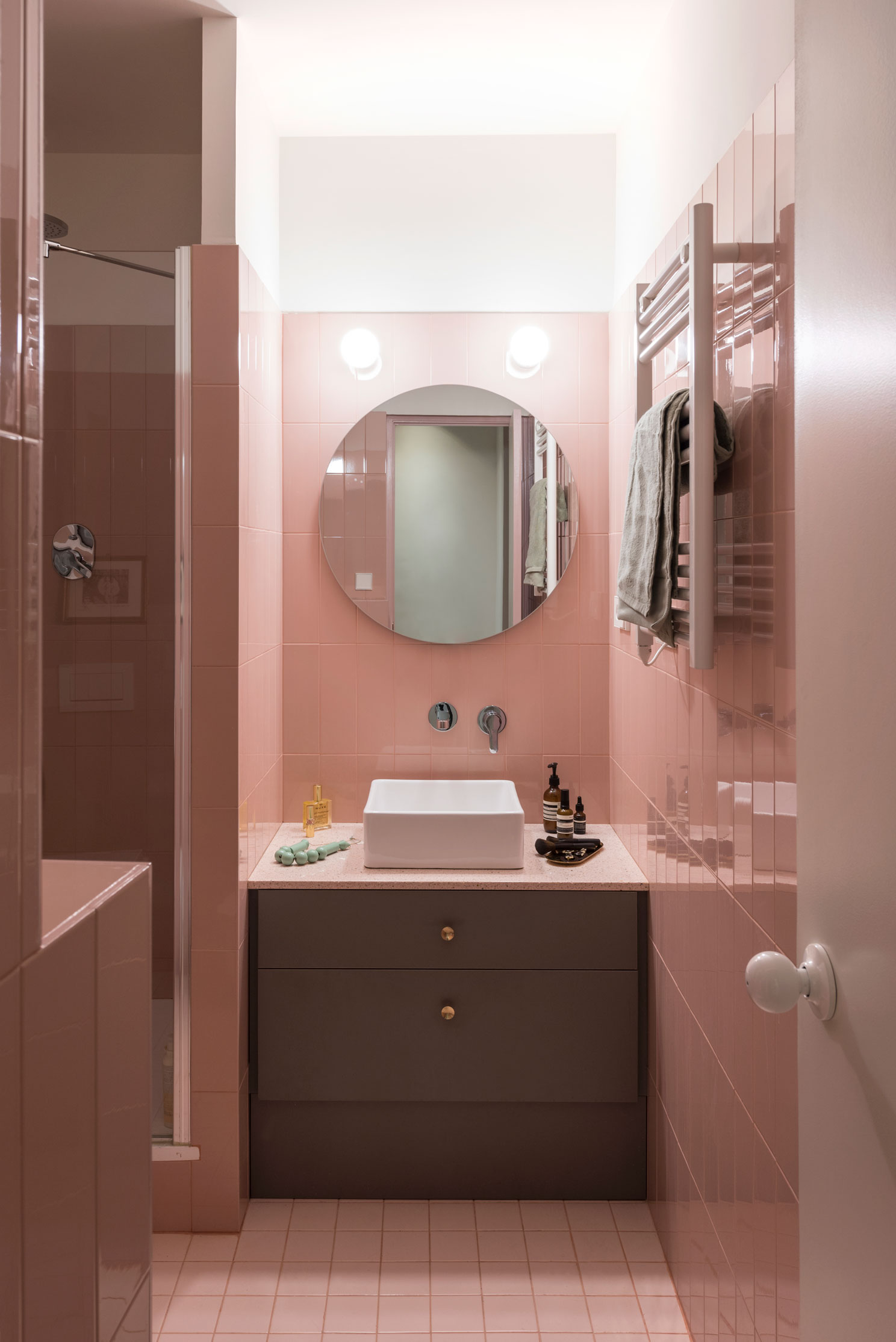 The master bathroom follows the subtle pink palette , clad with vertical 10x30cm ceramics by Ribesalbes and 10x10 floor tiles by  Vogue. All the counters are made with a pink terrazzo-like quartz finish.