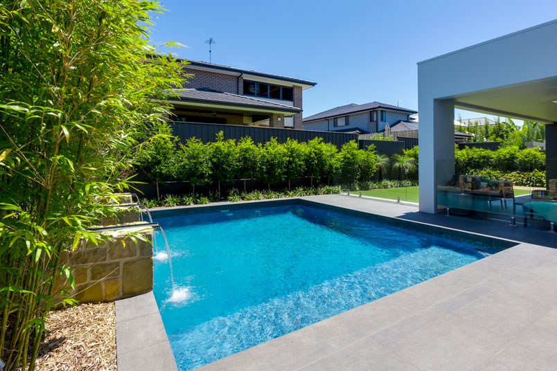 """""""The pool and the landscaping complement the tailored luxury of the home. By day it's a pretty nice feature but with the lights in the pool and water feature it really comes alive at night. """""""