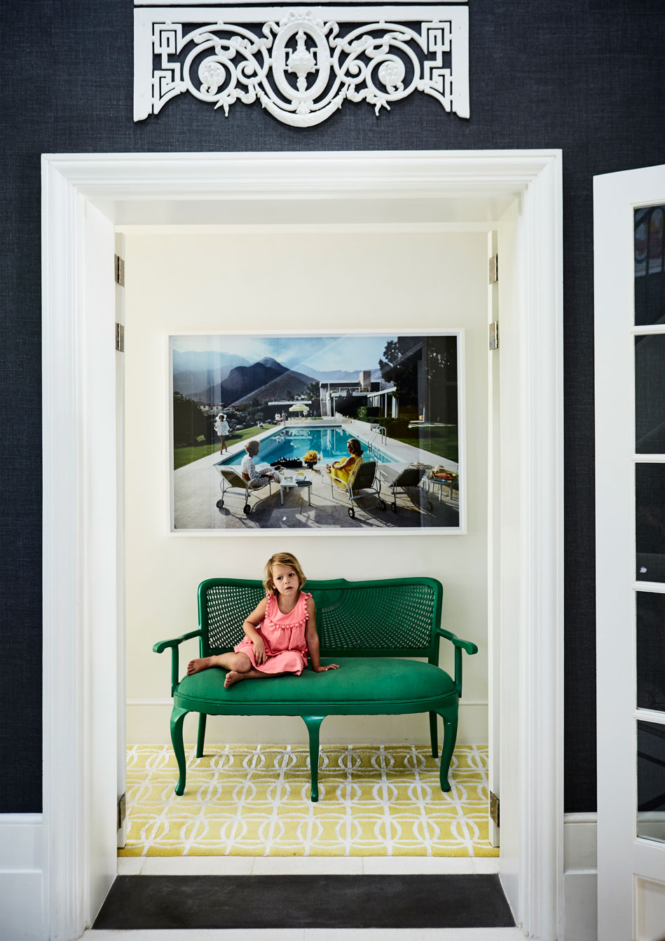Anna seated on the bright green sofa that adorns the entranceway to the guest cloakroom and guest suite. 