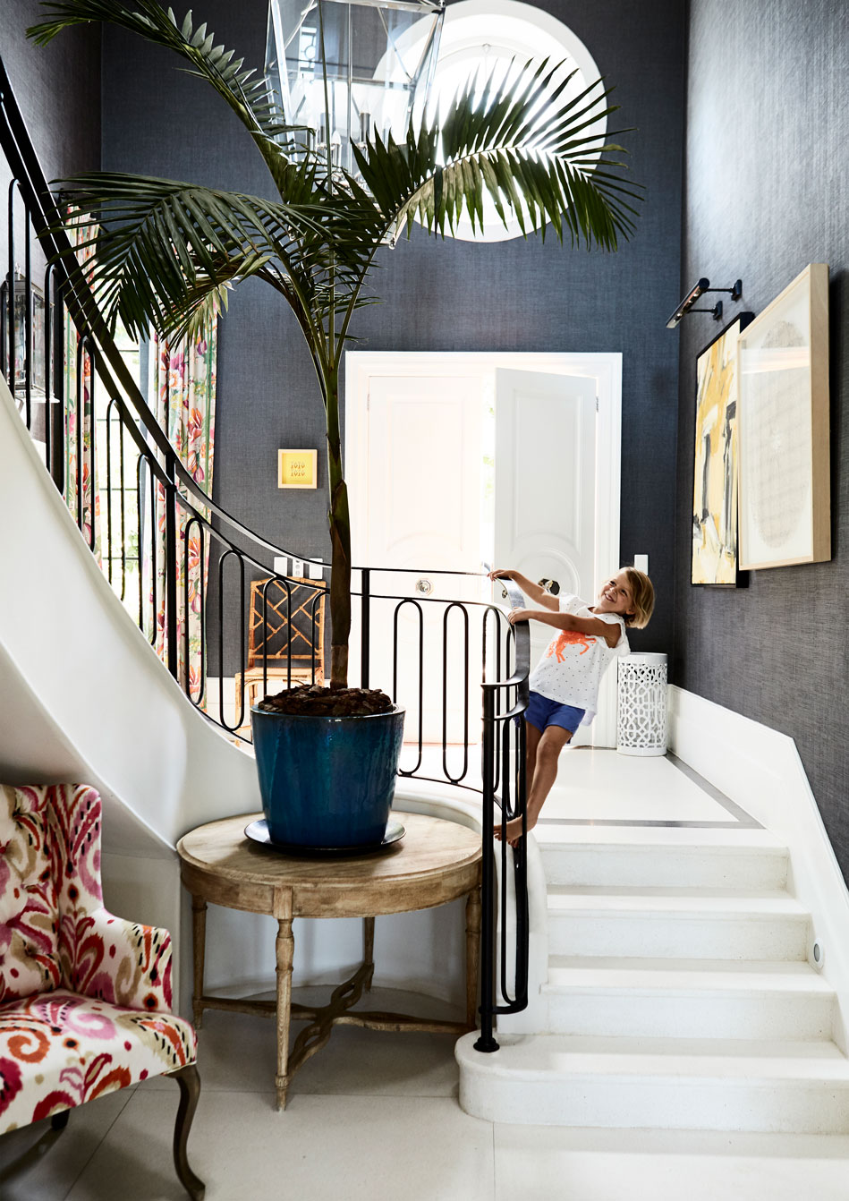 Homeowner and interior designer Kim Stephen!&s daughter Anna at play in the elegant entrance hall and stairwell. Key decor elements here include a textured grey wallpaper.