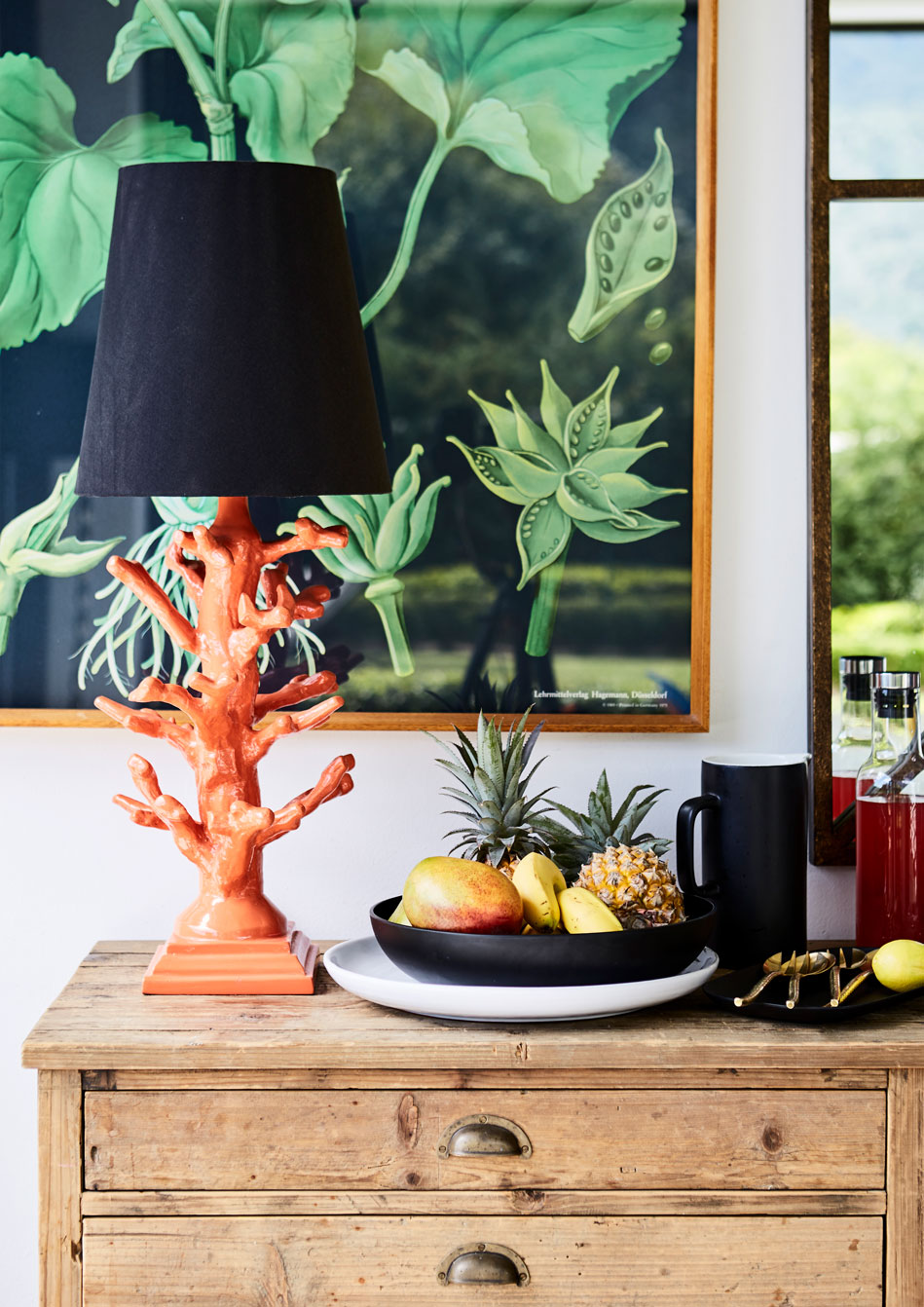 In the dining space of the 'outdoor room' or patio area, the multi-drawer wooden sideboard and the bright orange, coral-inspired lamp are both from Block & Chisel (blockandchisel.co.za). The botanical artwork is a Jung-Koch-Quentell teaching panel, available through Hagemann.