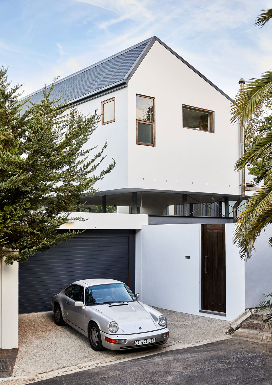 From the street, the top storey of the home appears to be floating beyond the perimeter wall. The relatively low wall to the street allows the ground floor to also benefit from the mountain views.